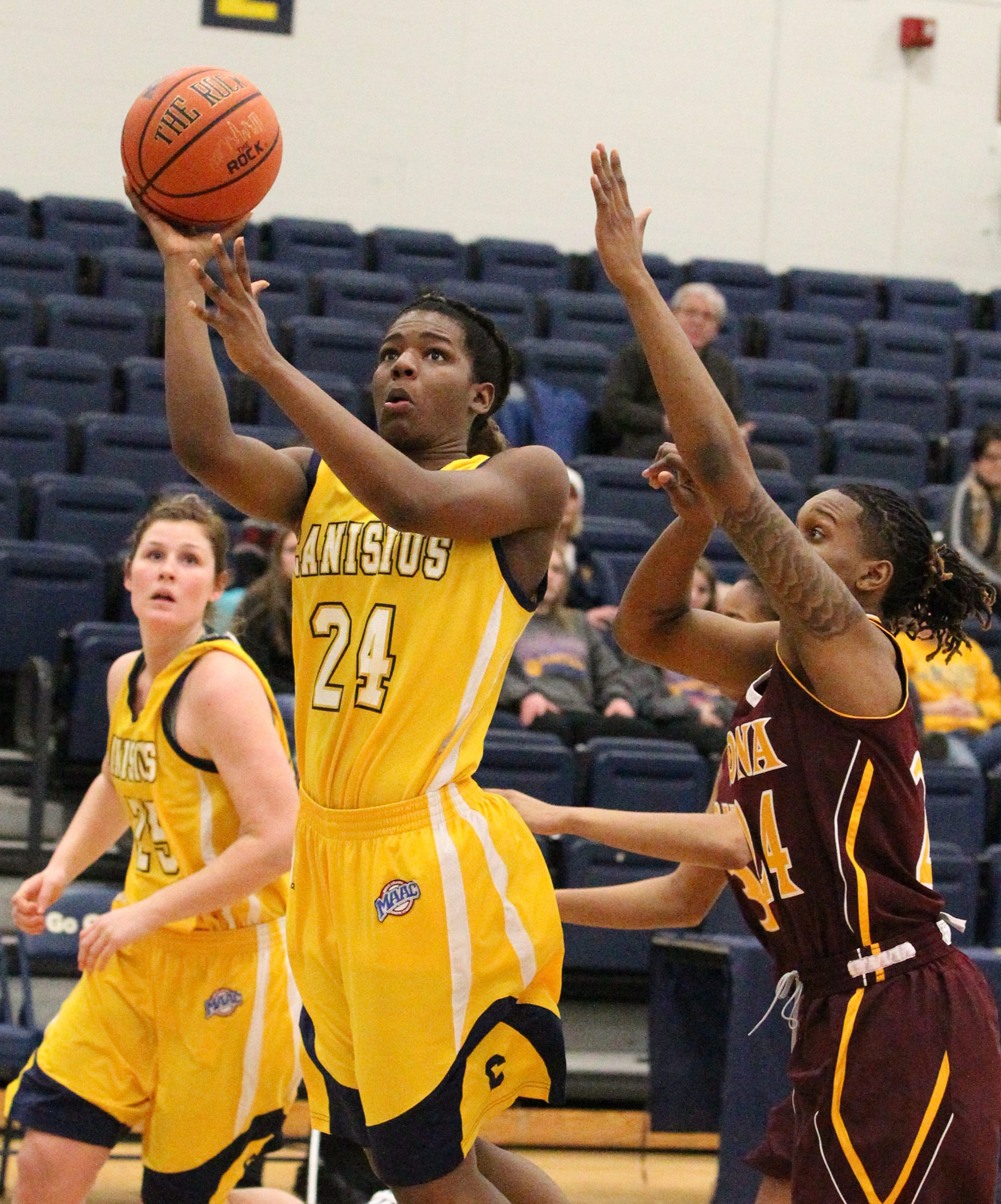Crystal Porter (24) of Canisius scores two points over Iona's Joy Adams (24) in the first half of Iona's victory at the Koessler Athletic Center.