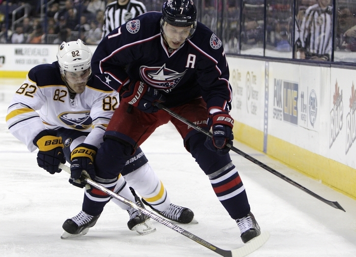 The Sabres' Marcus Foligno tries to get the puck from Columbus' Jack Johnson on Saturday. Foligno scored a short-handed goal in the Sabres' 5-2 victory. (Associated Press)