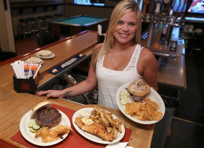 "Bartender Desiree Holdaway shows off the fish fry, ""regular"" burger and beef on weck at Sean Colins Irish Pub. (Charles Lewis/Buffalo News)"