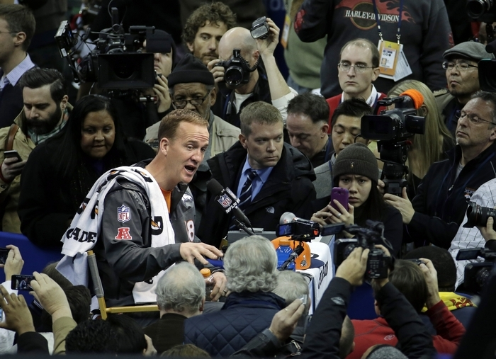 Peyton Manning answers questions from the horde of journalists at Super Bowl XLVIII Media Day. (Associated Press)