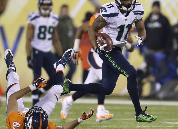 Seattle's Percy Harvin runs past Denver's Jacob Tamme for a touchdown during the second half. (Associated Press)