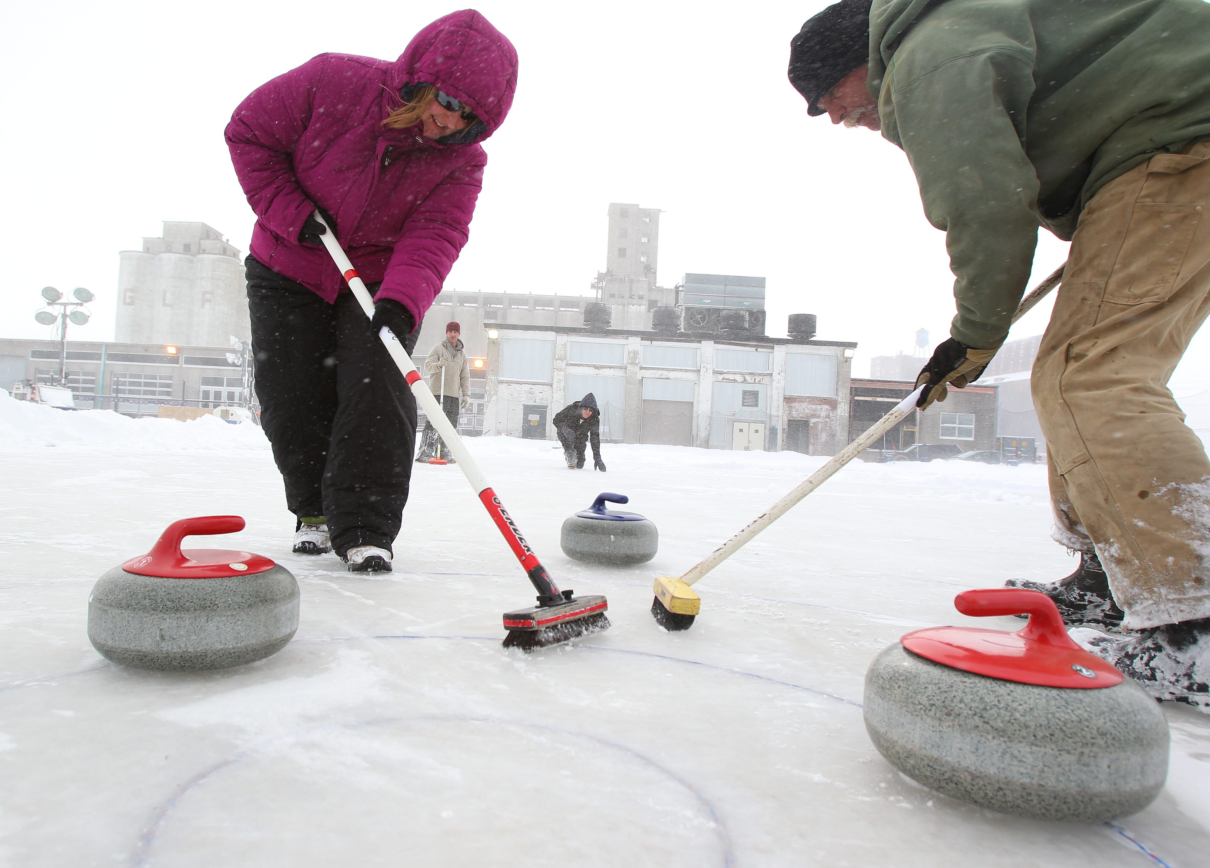 Local curlers – foreground, Danielle Buchbinder, left, and Rodney Cyrulik, and their teammates in background, Jeff Scott, center left, and Michael Rupp – get a workout at Buffalo RiverWorks.