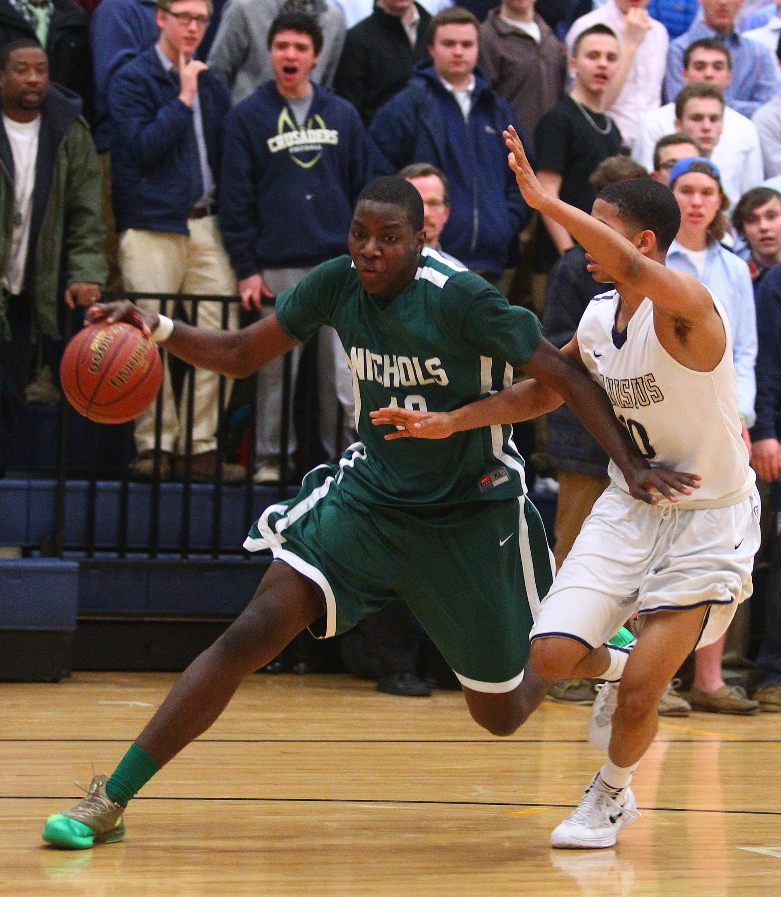 Cam Lewis of Nichols, driving around Canisius defender Howard Washington, led the Vikings with 22 points as they knocked off the No. 1 large school, 57-50.