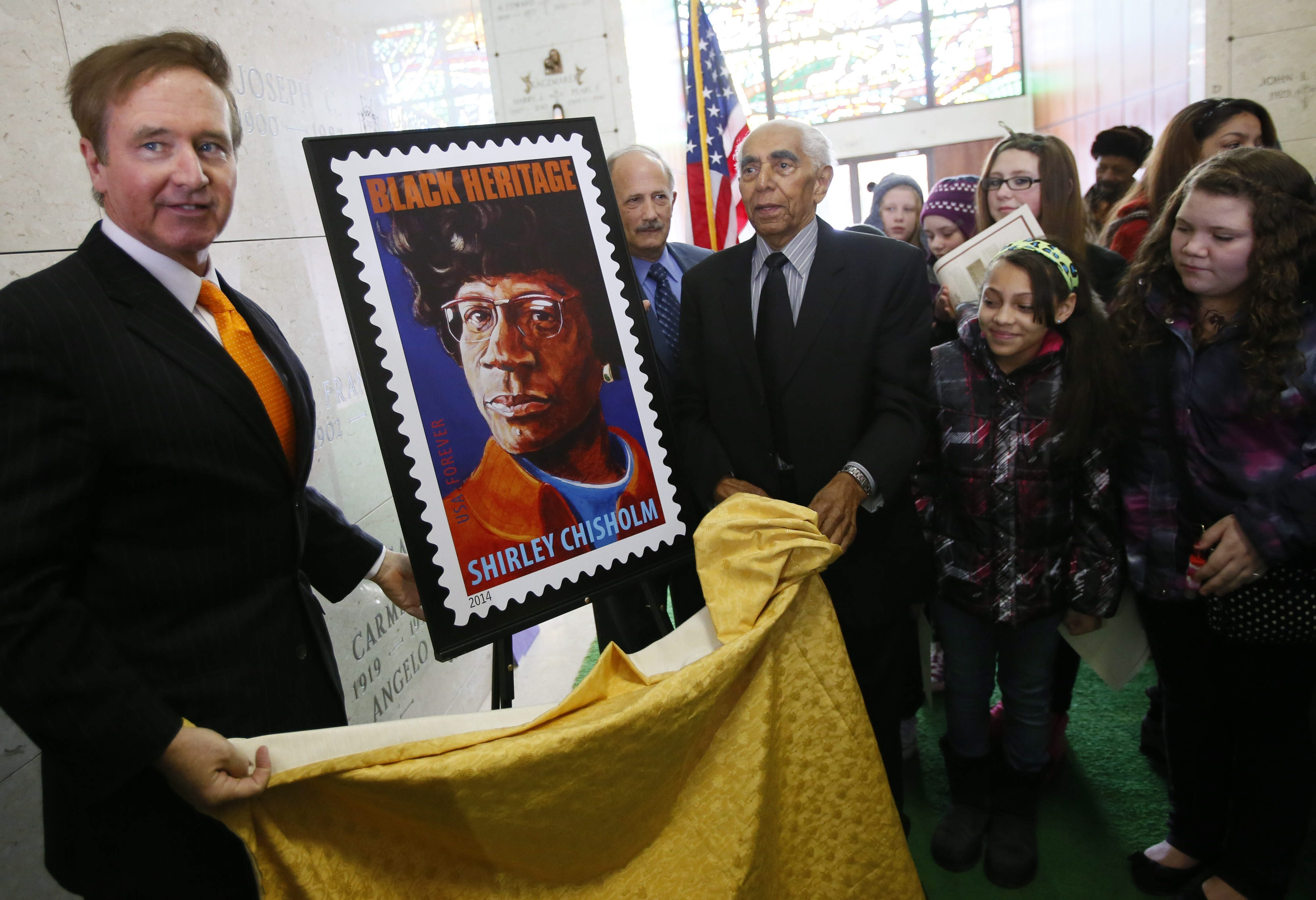 Rep. Brian Higgins, left, and Frank Mesiah, head of the Buffalo branch of the NAACP, unveil a U.S. Postal Service stamp honoring Shirley Chisholm on Tuesday in Forest Lawn, where Chisholm is entombed.