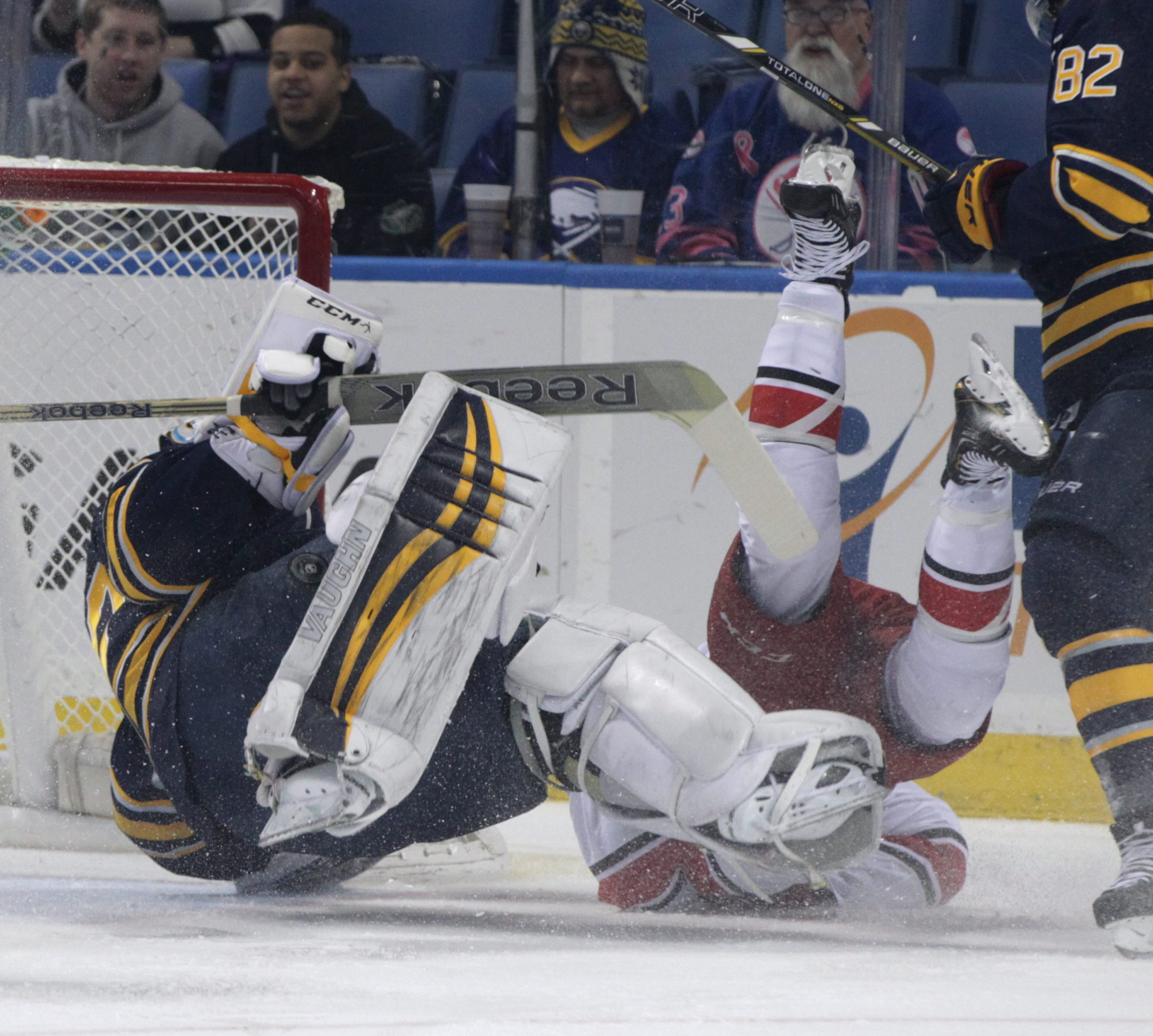 It's off their feet for Buffalo Sabres goalie Ryan Miller and Carolina Hurricanes center Riley Nash during the first period.