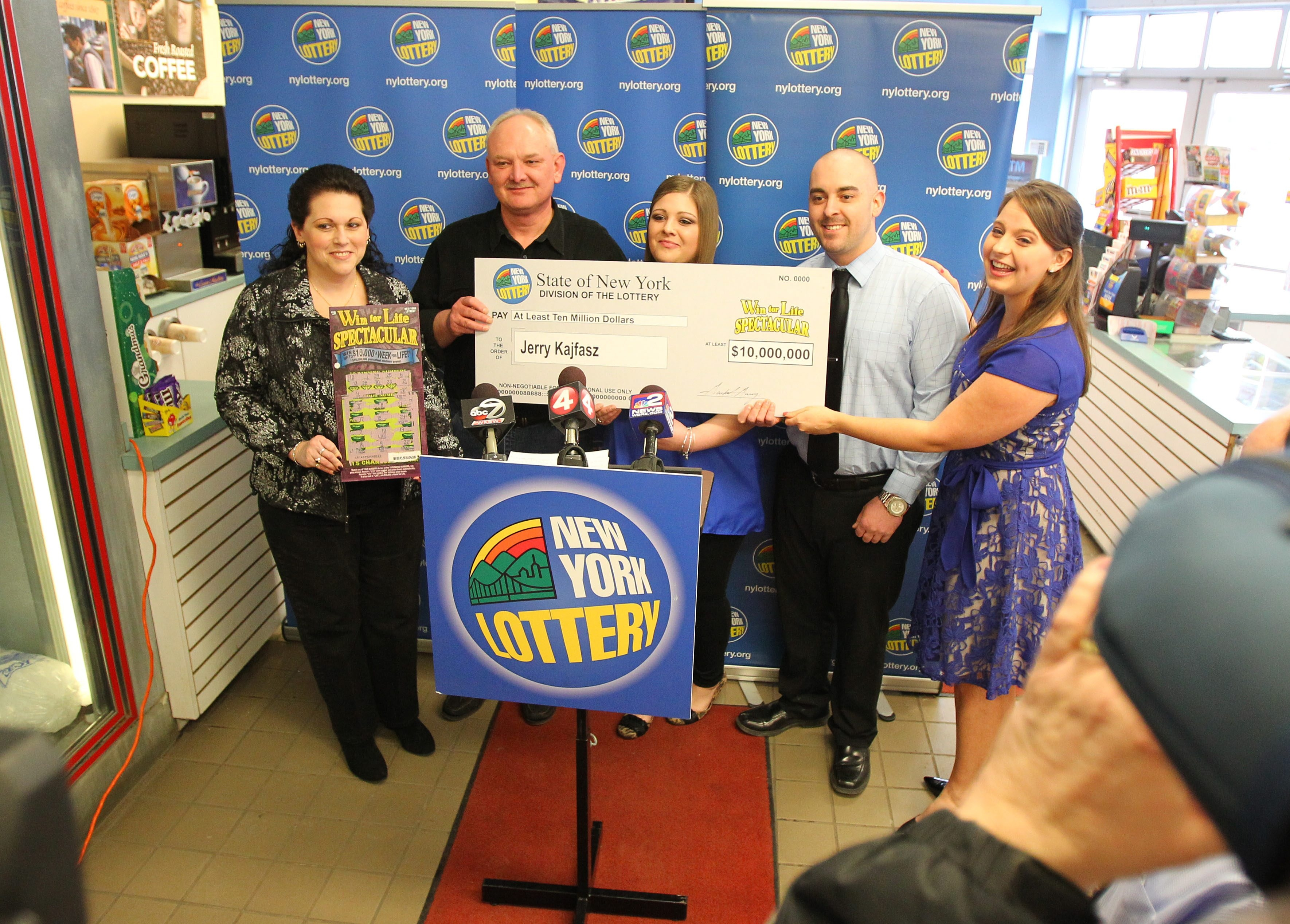 The Kajfasz family, from left, Anne, Jerry, Jackie and Frank, accept a ceremonial check from New York Lottery's Gretchen Dizer, right, Tuesday.