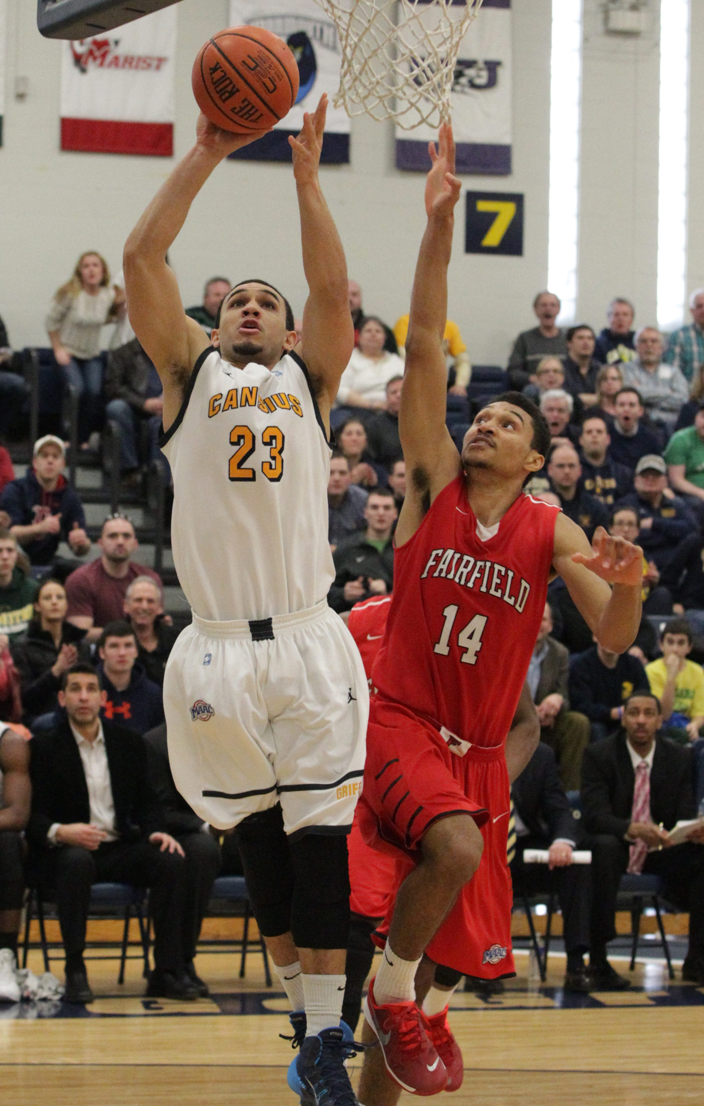 Chris Perez (23) of Canisius scores over Fairfield's Marcus Gilbert (14) in the second half.