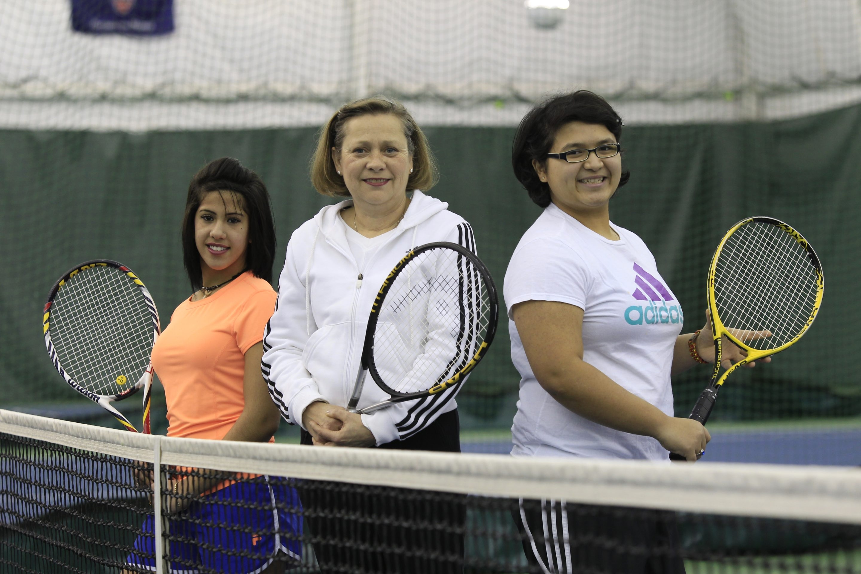 Marsha Huard, center, founder of the River Rock Tennis Association, has taught students Hanni That, left, of Mount St. Mary's and Manar Ali of Health Sciences Charter, among others.