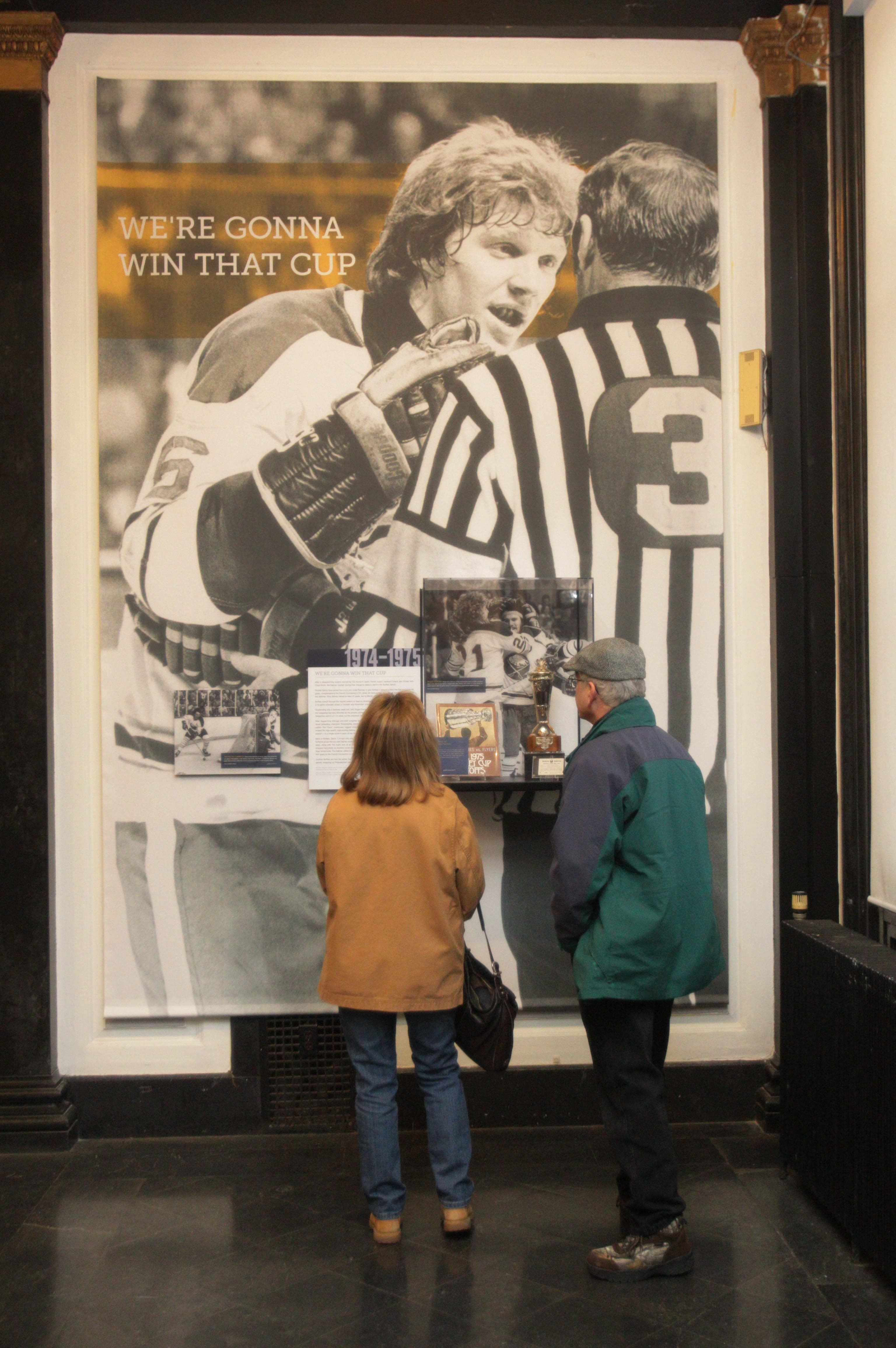 Patty and Edward Fries of East Amherst look at a panel about the Sabres' 1974-75 season when the team went to the Stanley Cup finals.