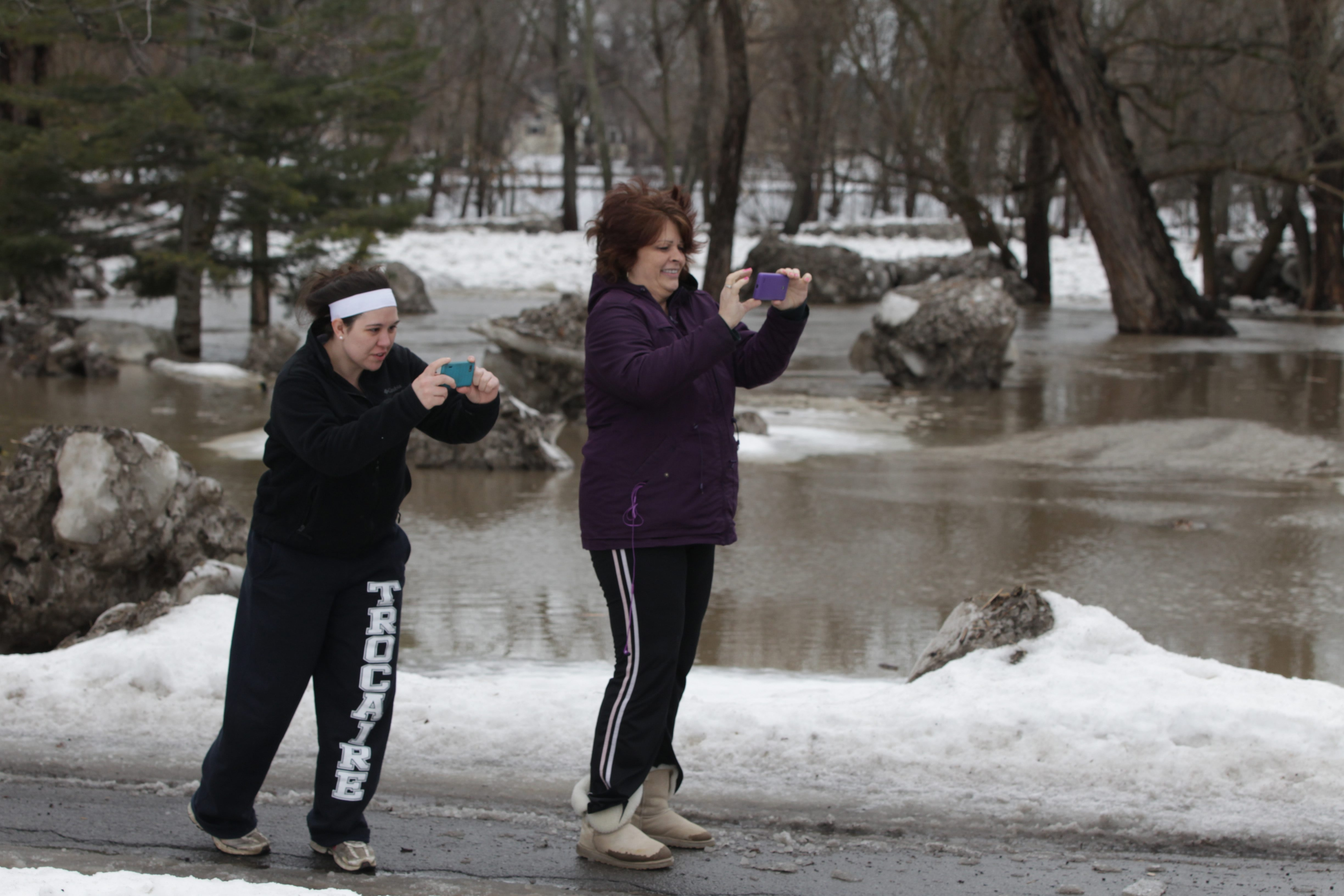 Victoria Mackey and Becky Safe take pictures of the flooding at Cazenovia Creek in Buffalo on Friday.