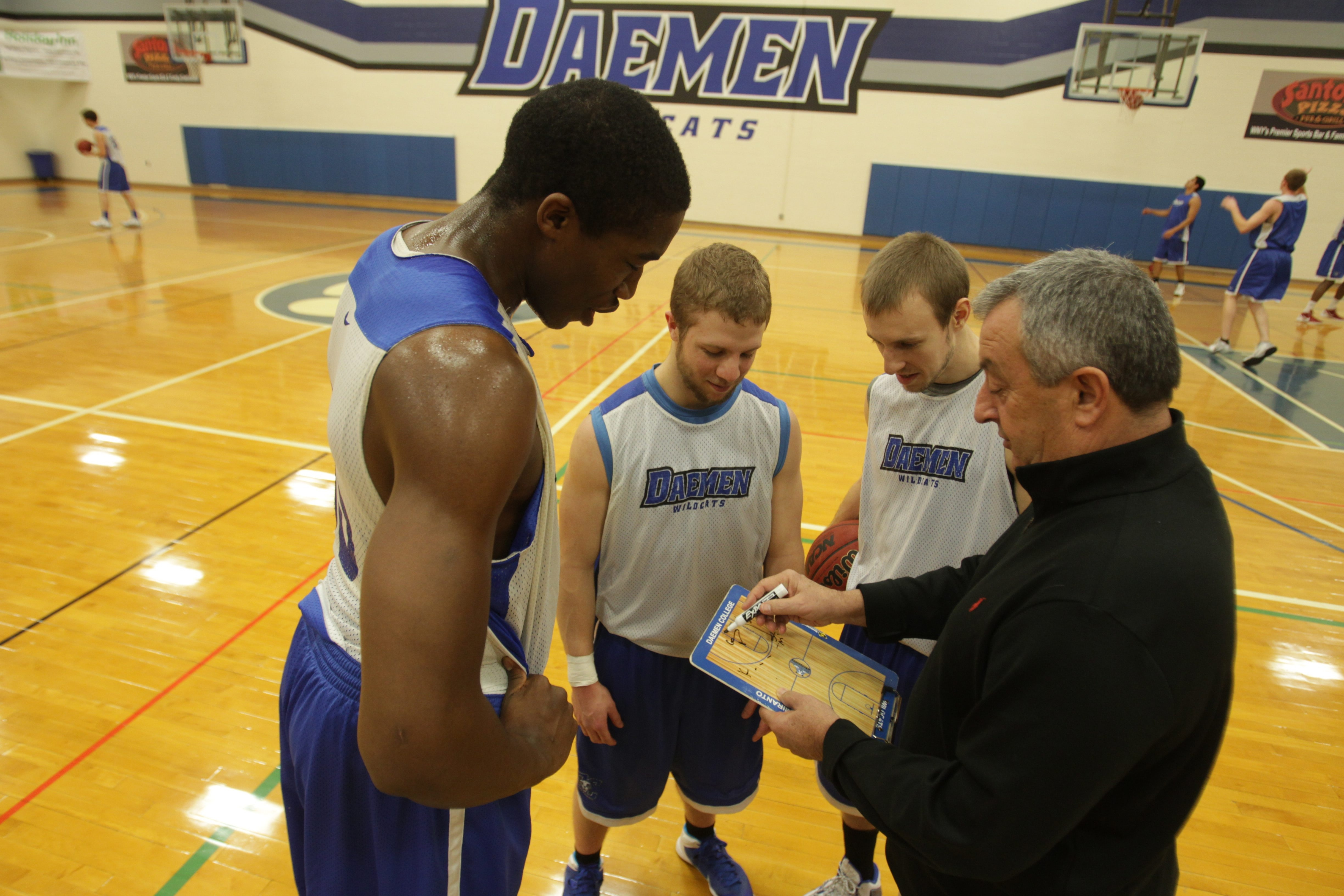 From left, key players Gerald Beverly, Casey Sheehan and Mark Coppola get pointers from Coach Don Silveri.