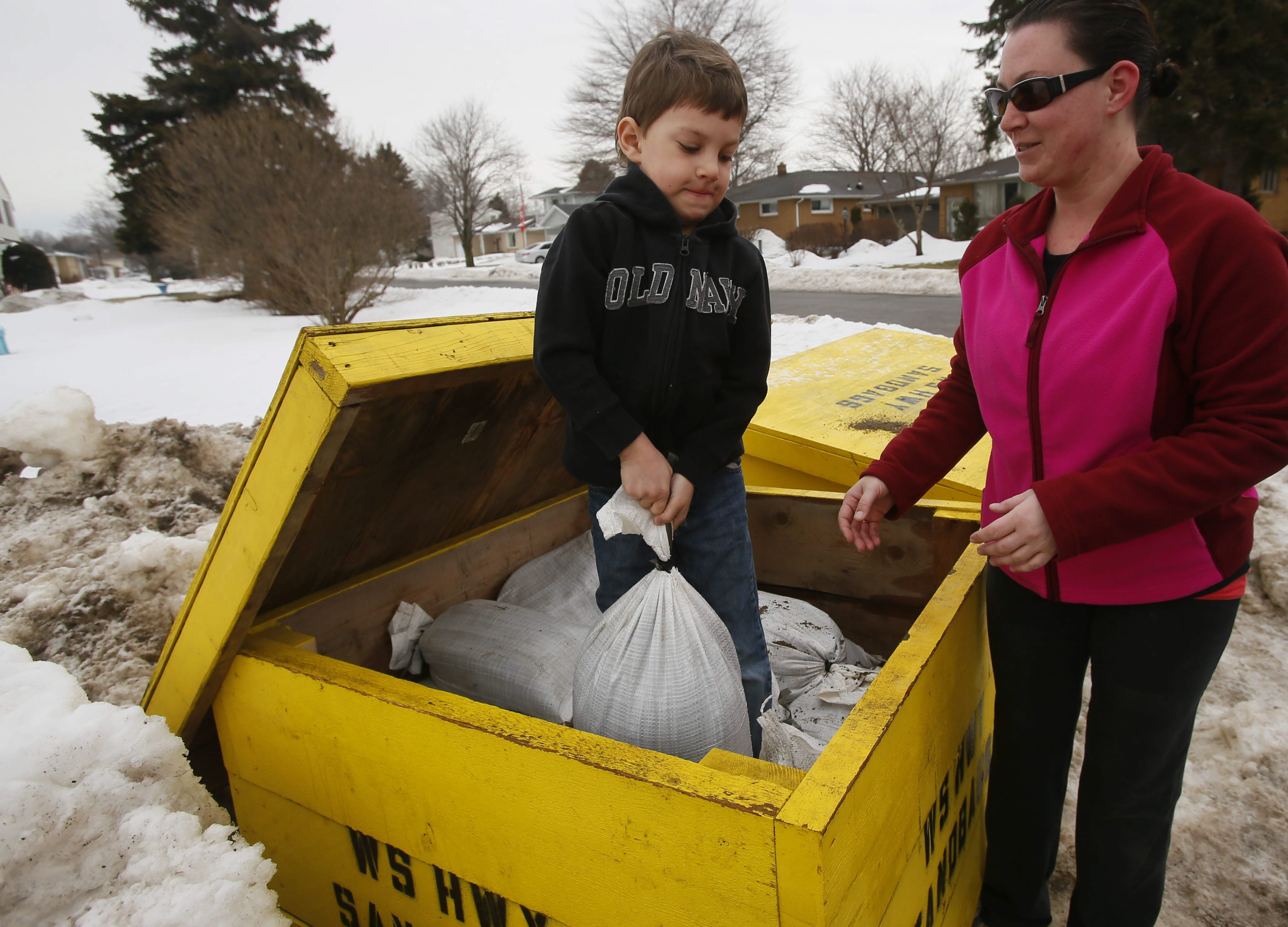 Damian Kazmierczak, 7, tries to lift a sandbag while helping his mother, Nicole Szablicki pick up sandbags made available by the West Seneca highway department in the Lexington Green neighborhood of West Seneca as residents prepare for the potential of flooding due to the warm temperatures.