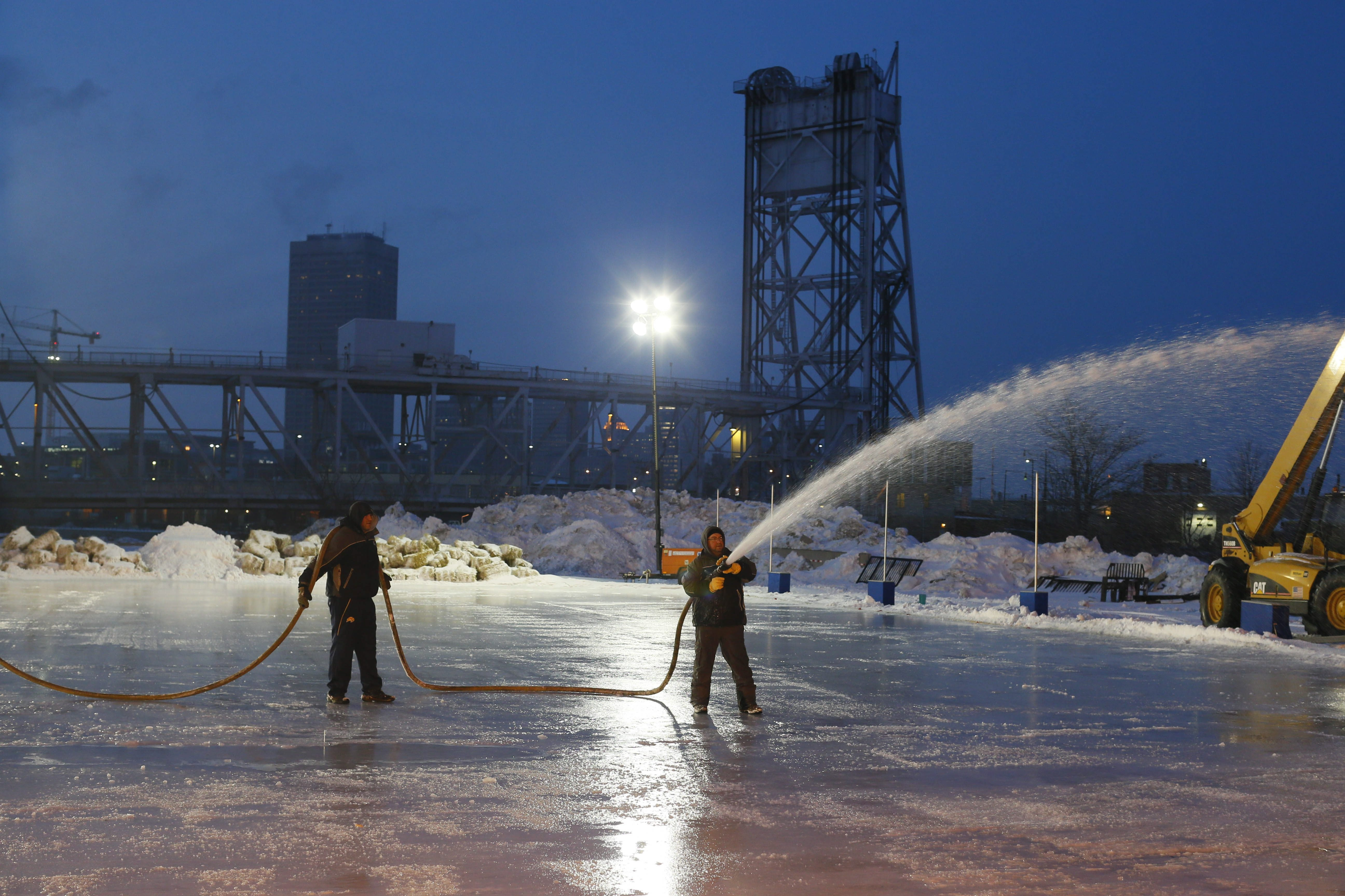 From left, Jason Sattelberg and Peter Cicero are among the crew flooding the ice surface to prepare Buffalo RiverWorks' ice rinks for the Labatt Blue Pond Hockey Tournament.