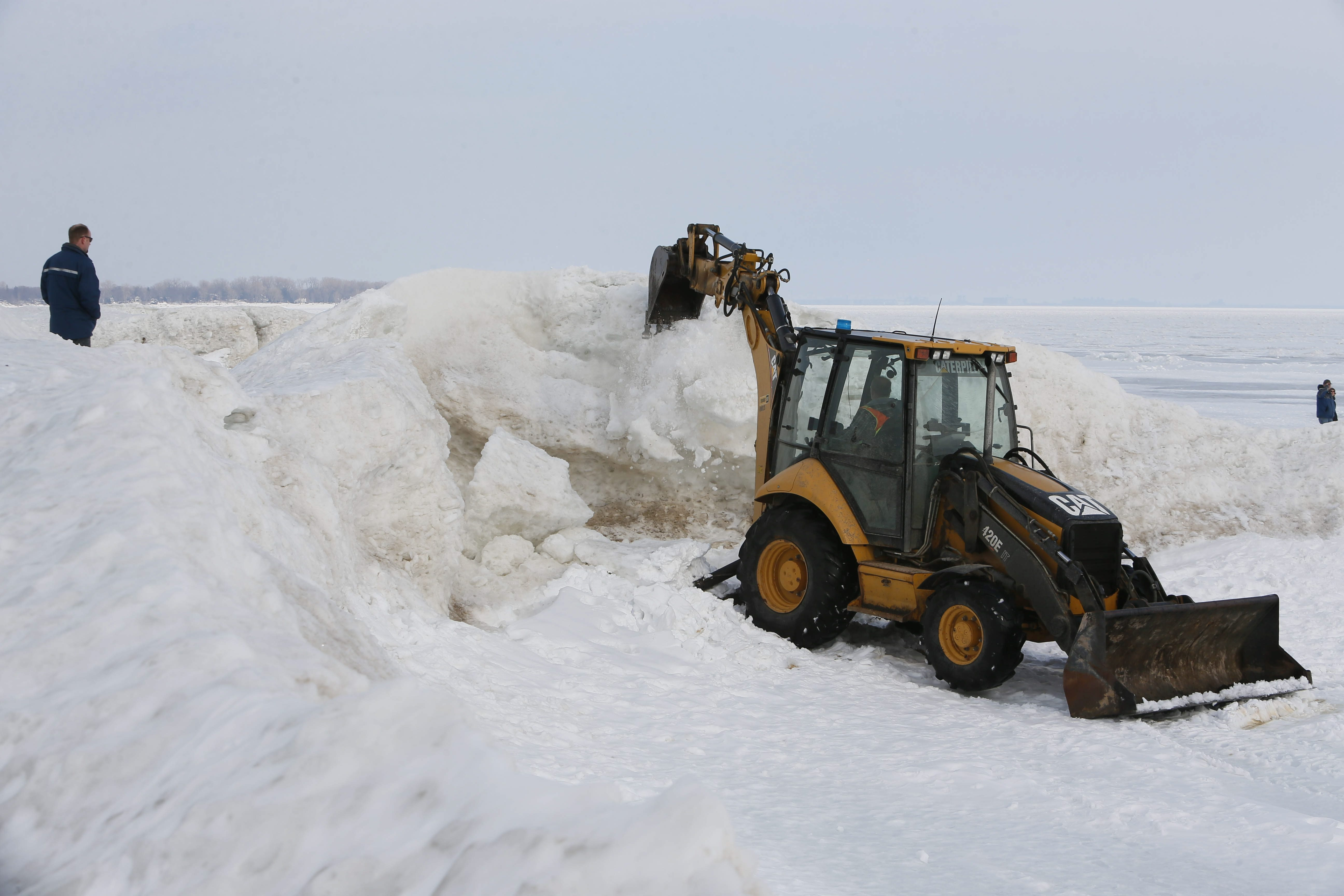 A backhoe knocks down the ice caves at Crystal Beach Wednesday after the formations had become unsafe.
