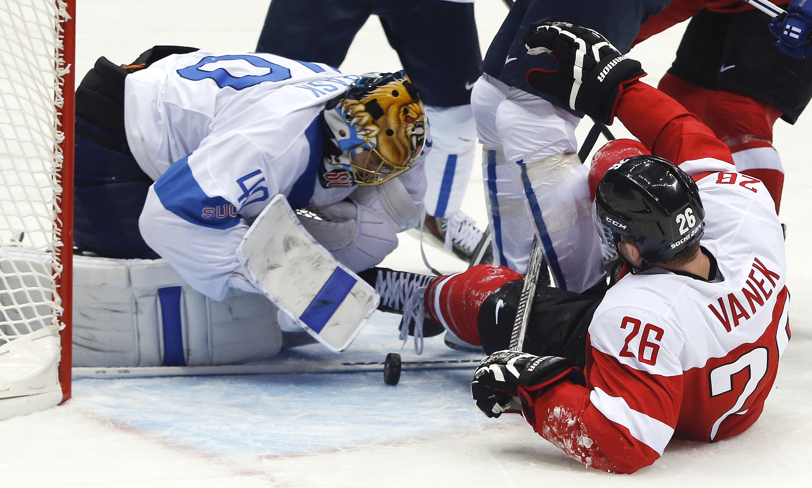 Austria forward and former Buffalo Sabres captain Thomas Vanek falls to the ice as Finland goaltender Tuukka Rask reaches to smother a rebound in the first period of a men's ice hockey game at the 2014 Winter Olympics. (AP Photo/Julio Cortez)