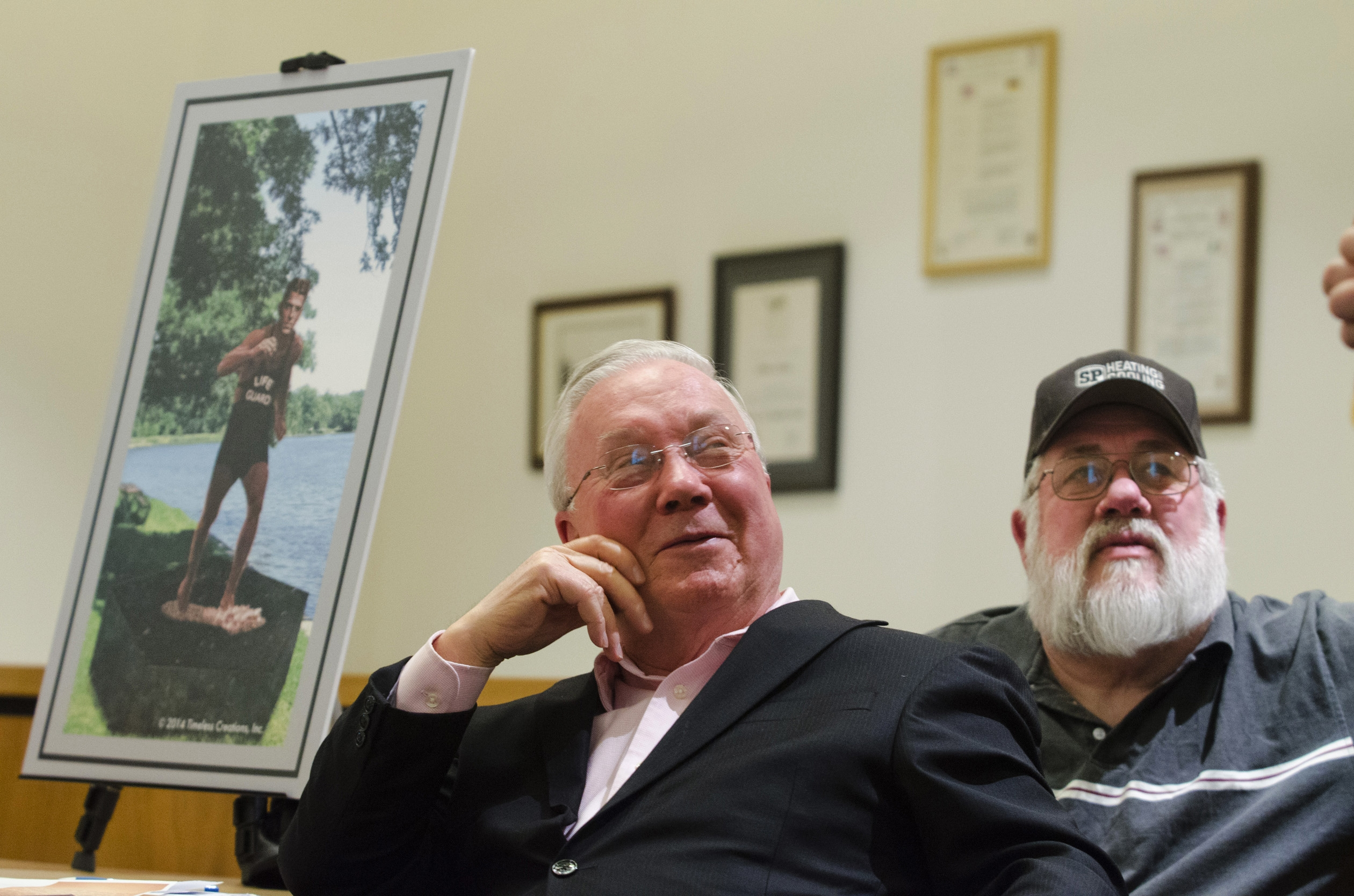 Dixon, Ill., Mayor Jim Burke sits with a rendering of a the proposed statue of lifeguard Ronald Reagan.