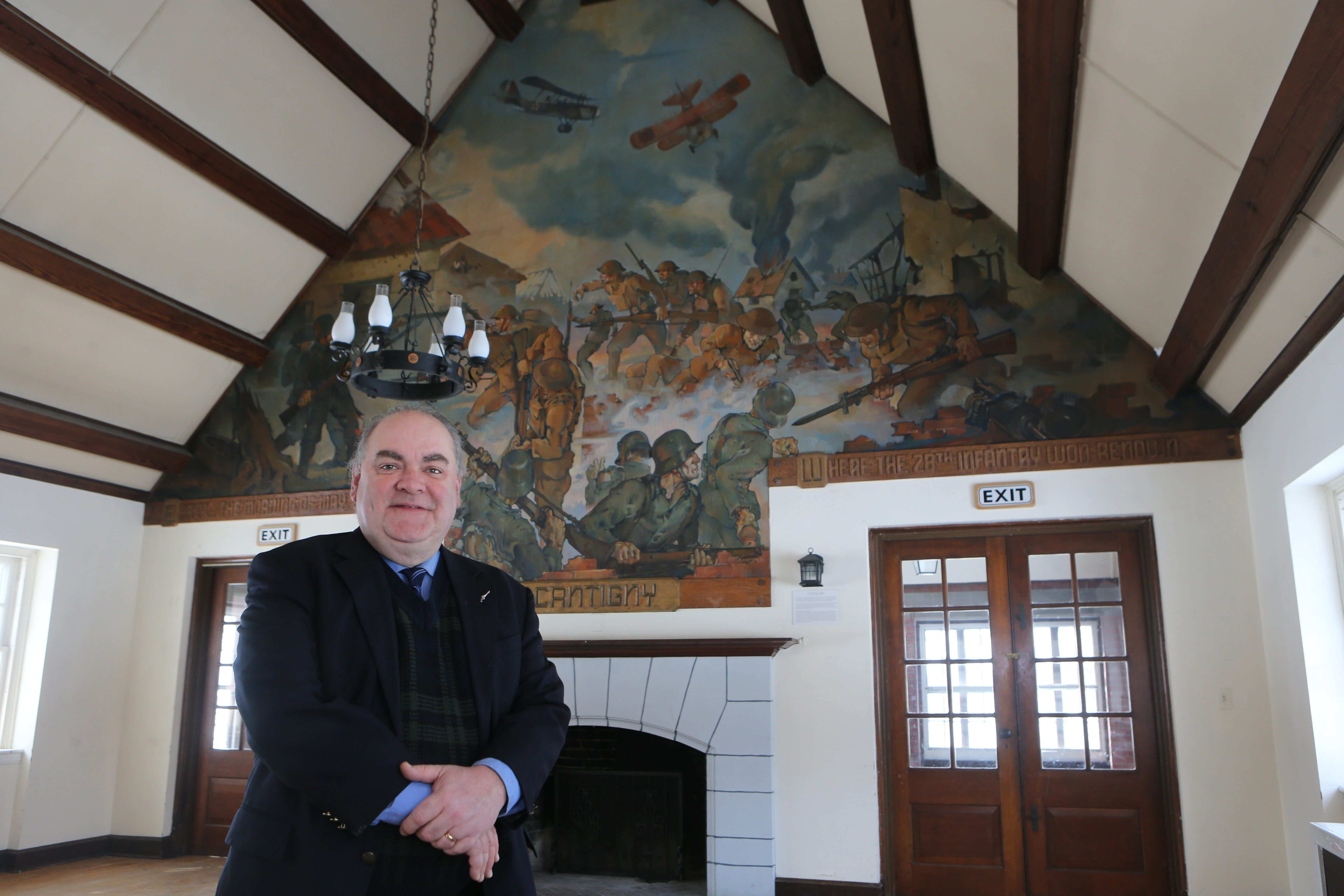 Robert Emerson, executive director of Old Fort Niagara, stands in front of the mural created by artist Hubert H. Crawford at the Officers Club in Fort Niagara State Park in Youngstown recently.