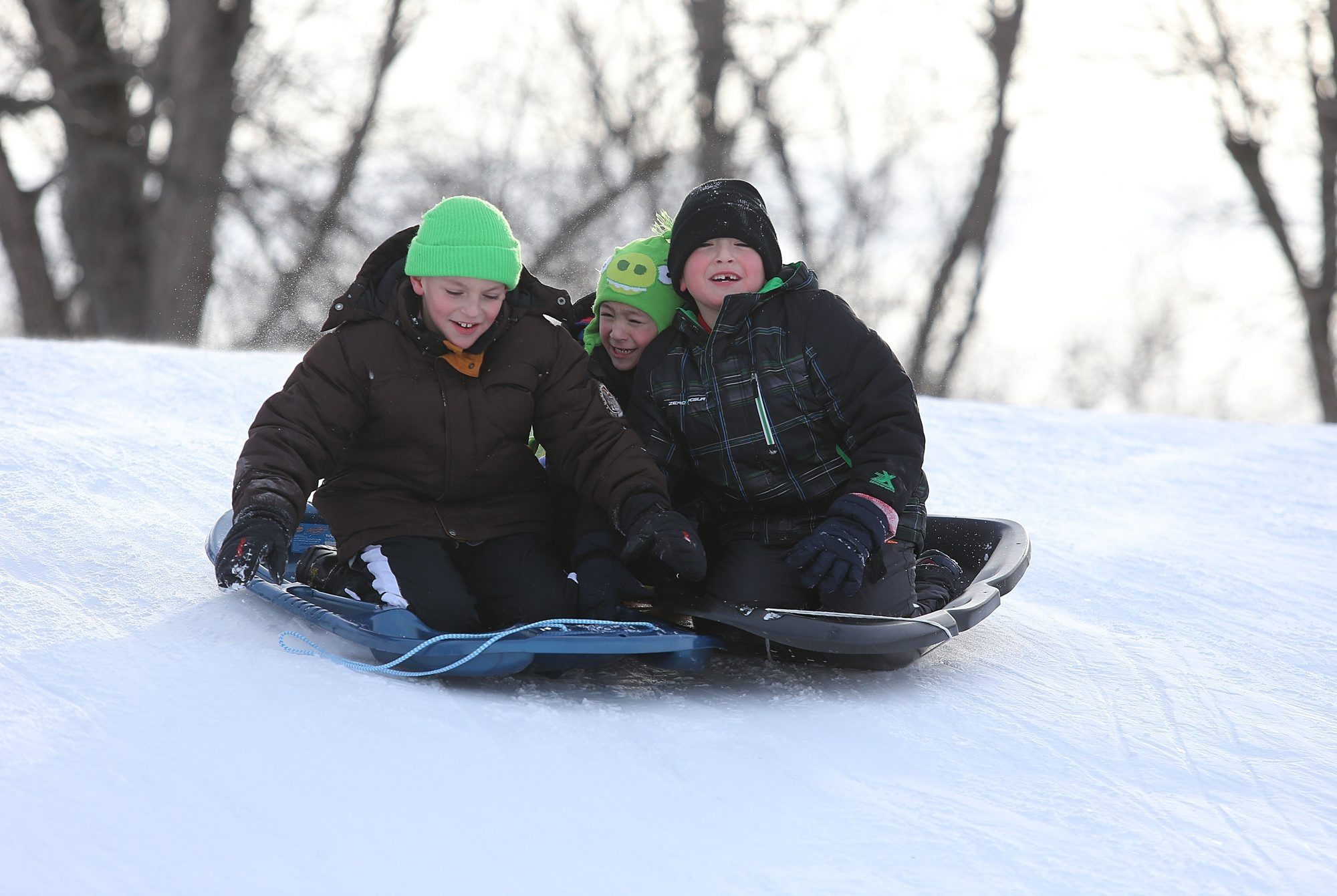 Sledders – from left, Andrew Roland, 9; Miguel Flores, 5; and Robbie Flores, 8 – enjoy hill at Ellicott Creek Park in Town of Tonawanda on Presidents Day holiday off from school.