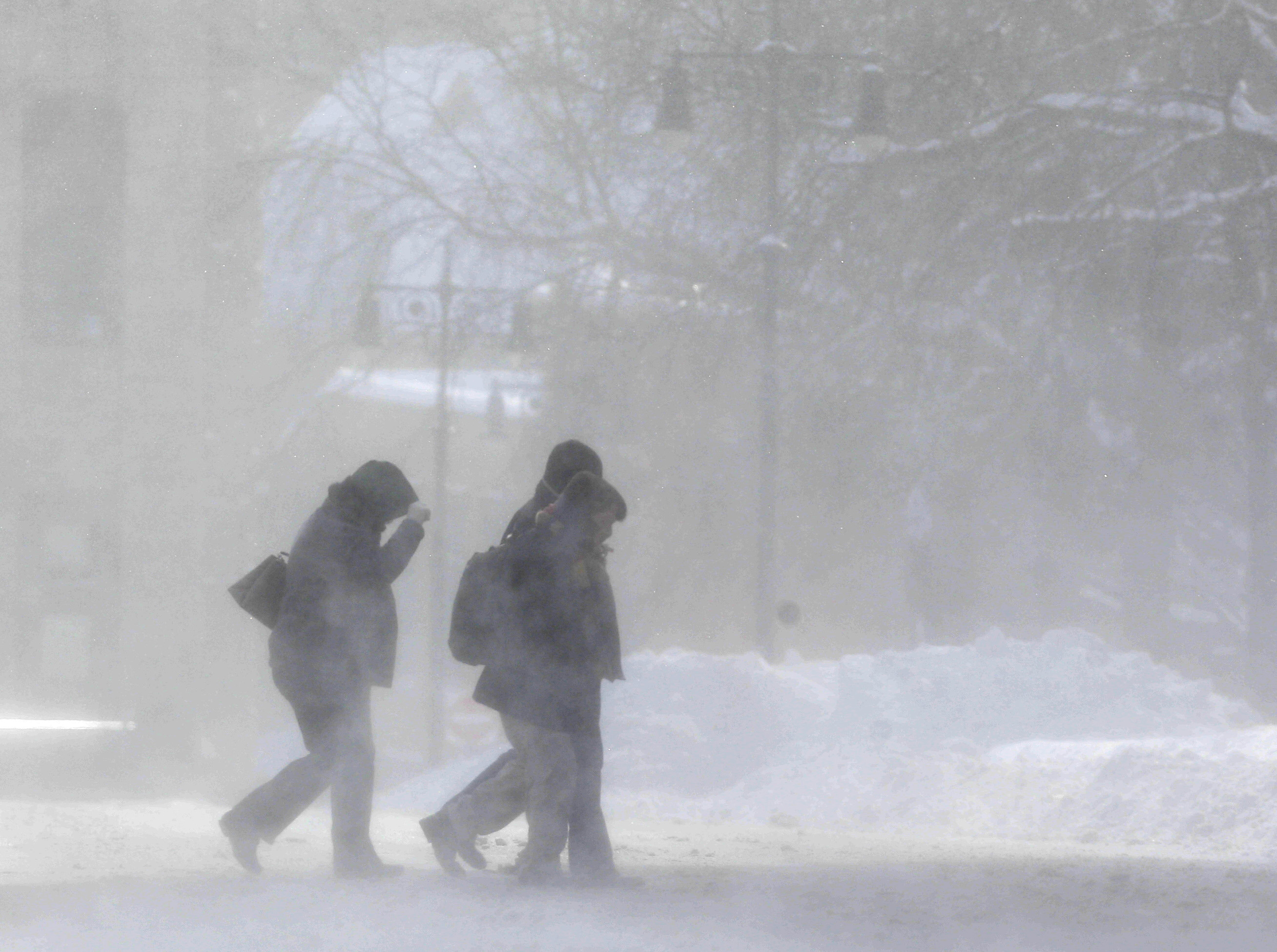 Pedestrians make their way through blowing snow on Friday along a street in Albany, N.Y. parts of upstate got more than 2 feet of snow.