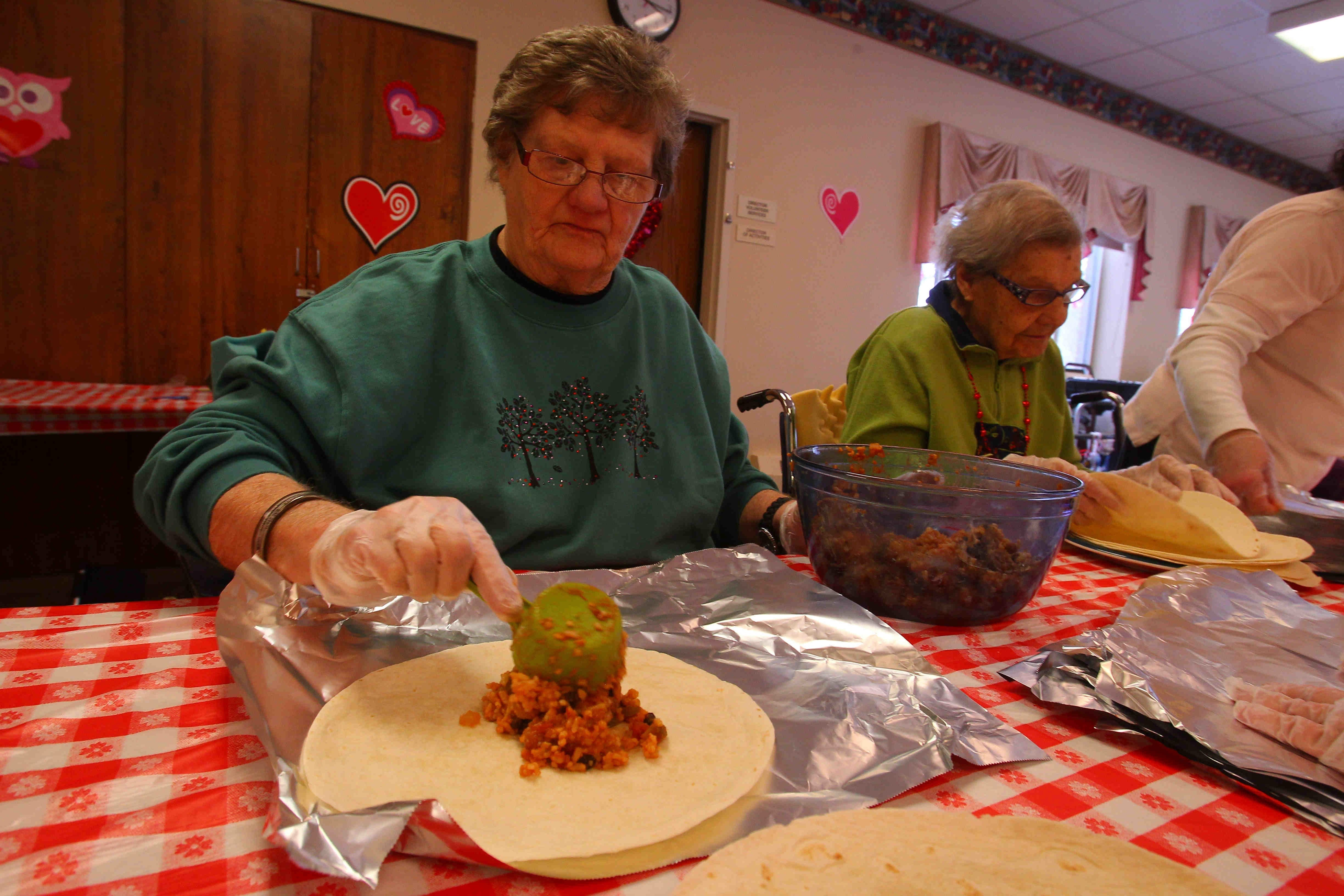 Faye Dills fills burritos at the monthly Burrito Project at Elderwood nursing home in Hamburg Tuesday. Residents of Elderwood gather and make burritos that are distributed to the homeless on Buffalo streets.