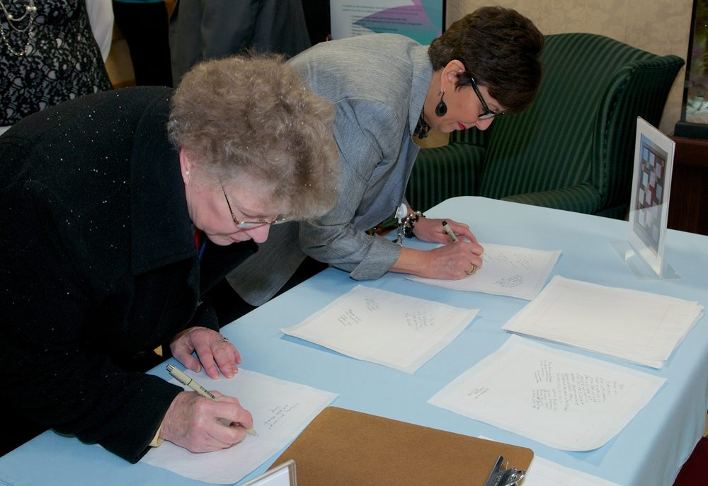 Niagara Hospice volunteer Rita Beitz, left, and Niagara Hospice Clinical Director Janet Ligammari pen messages on the quilt squares.