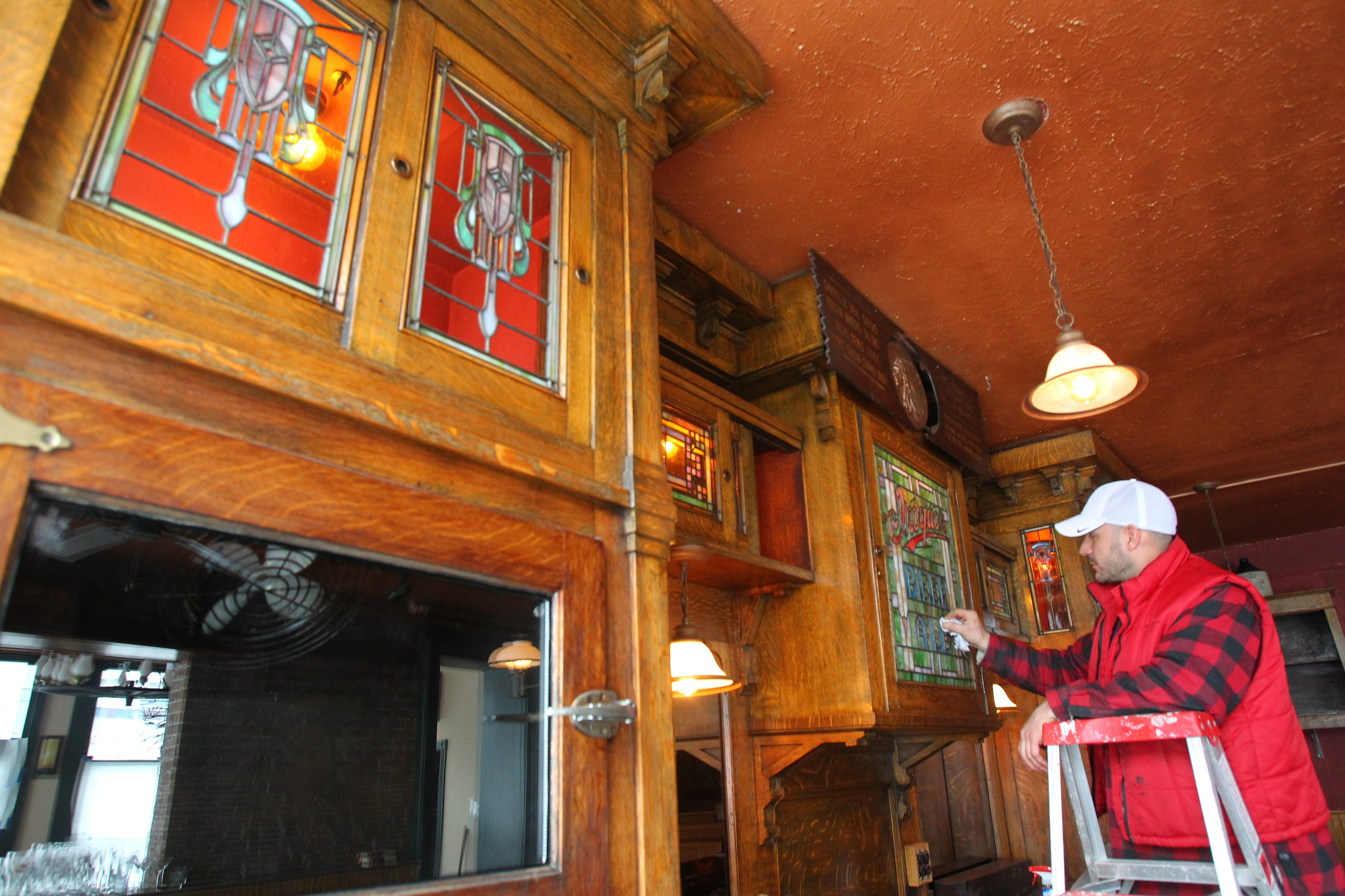 Sal Buscaglia cleans the antique bar at Ulrich's Friday. The tavern will be open for lunch and dinner served from a new kitchen.