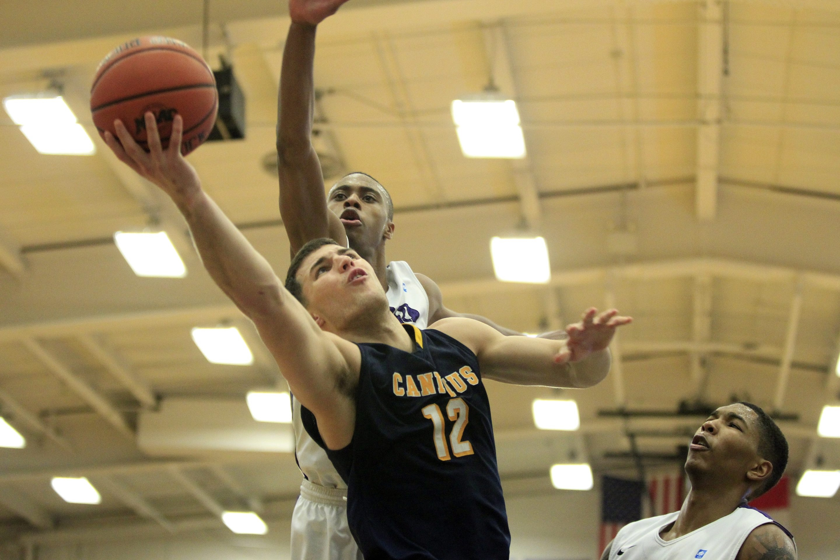 Billy Baron of Canisius slices past Tahjere McCall of Niagara during the second half.
