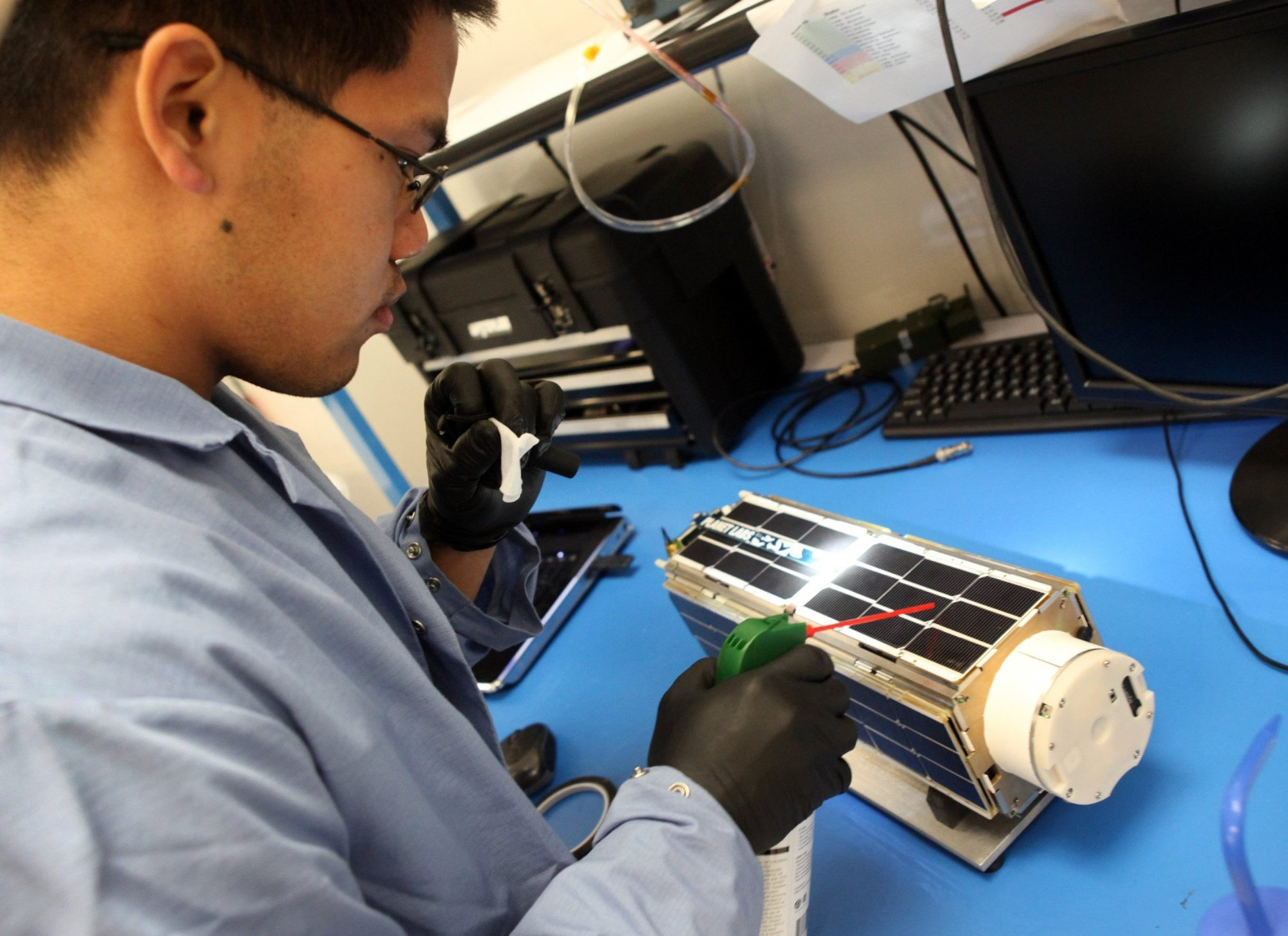 Mechanical engineer Alexander Wen works on a satellite camera at Planet Labs in San Francisco. Dozens of the devices were sent to the International Space Station for deployment.