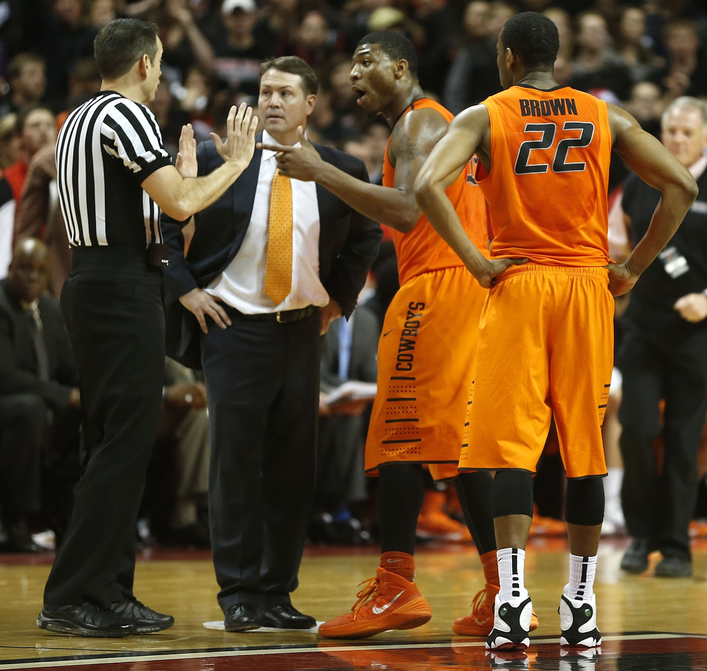 Oklahoma State coach Travis Ford, center, listens to an official with Marcus Smart after Smart shoved a spectator in Lubbock, Texas.
