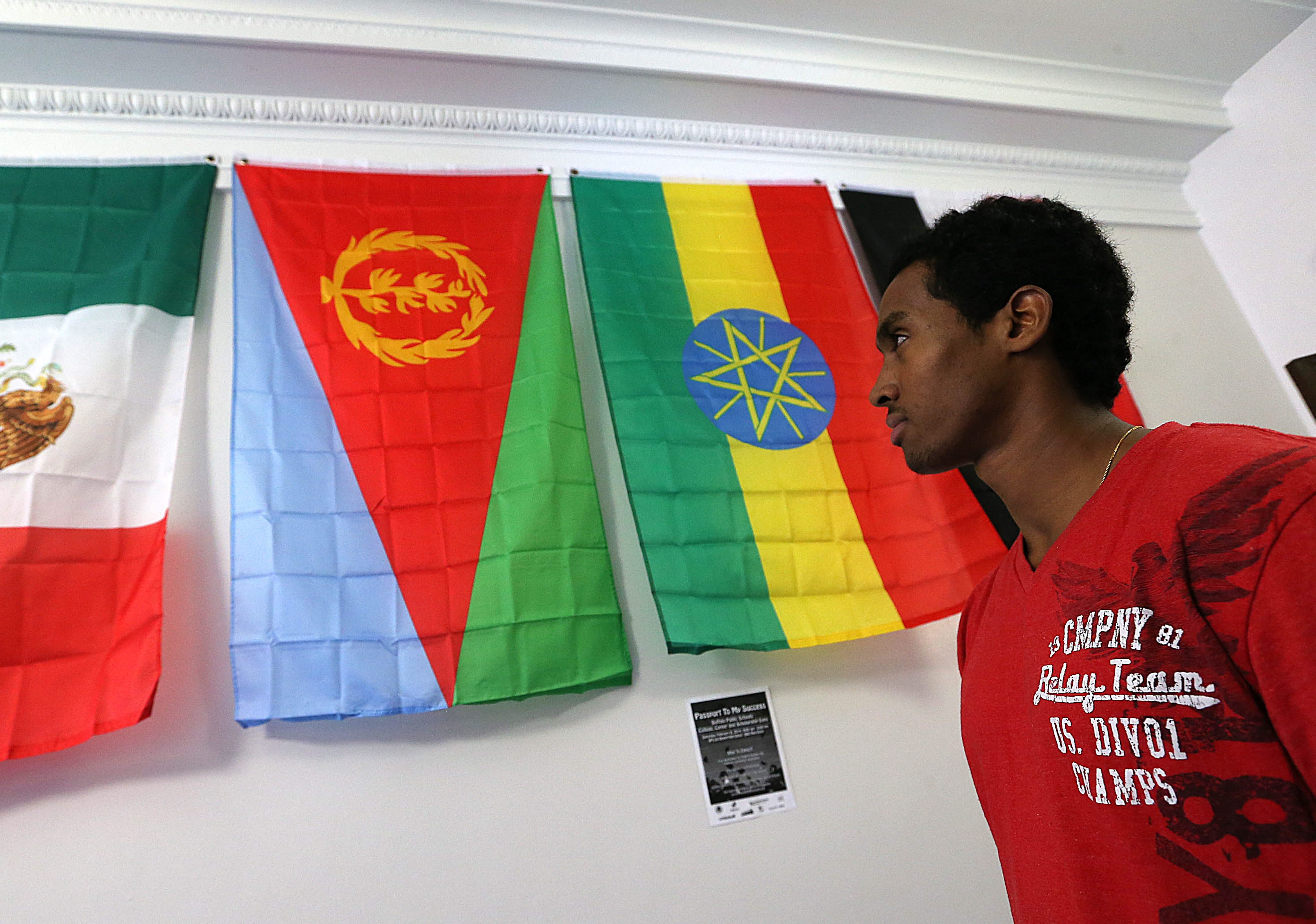Standing under the flag of his native Eritrea, middle, Ezana Kahsay has seen a lot in his young life.