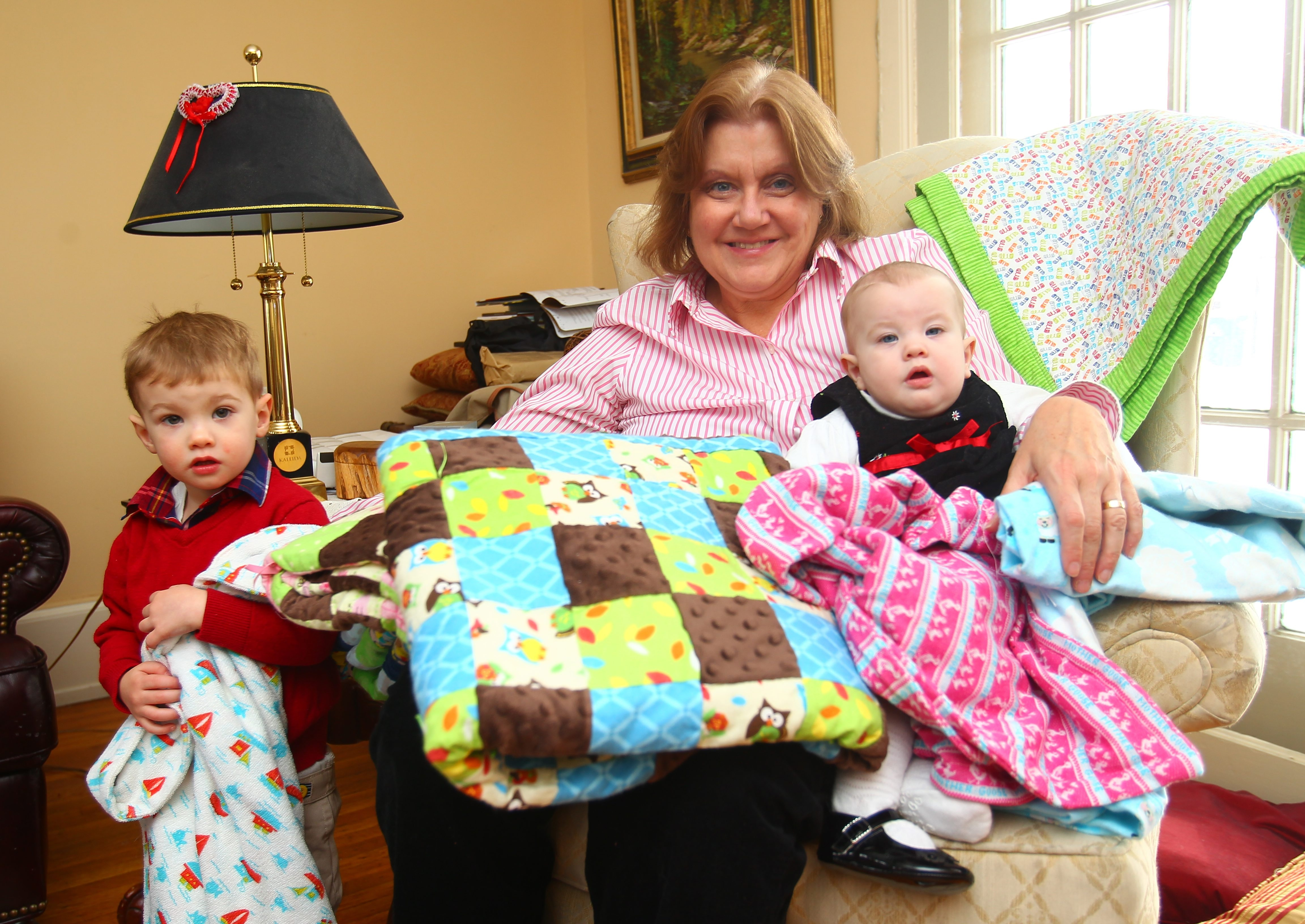 Pamela Riester shows off her grandchildren, Declan Beecher, 2, and Nora Beecher, 7 months, and a few of the 126 blankets she is giving to Project Linus. The blankets will be donated to children in need.