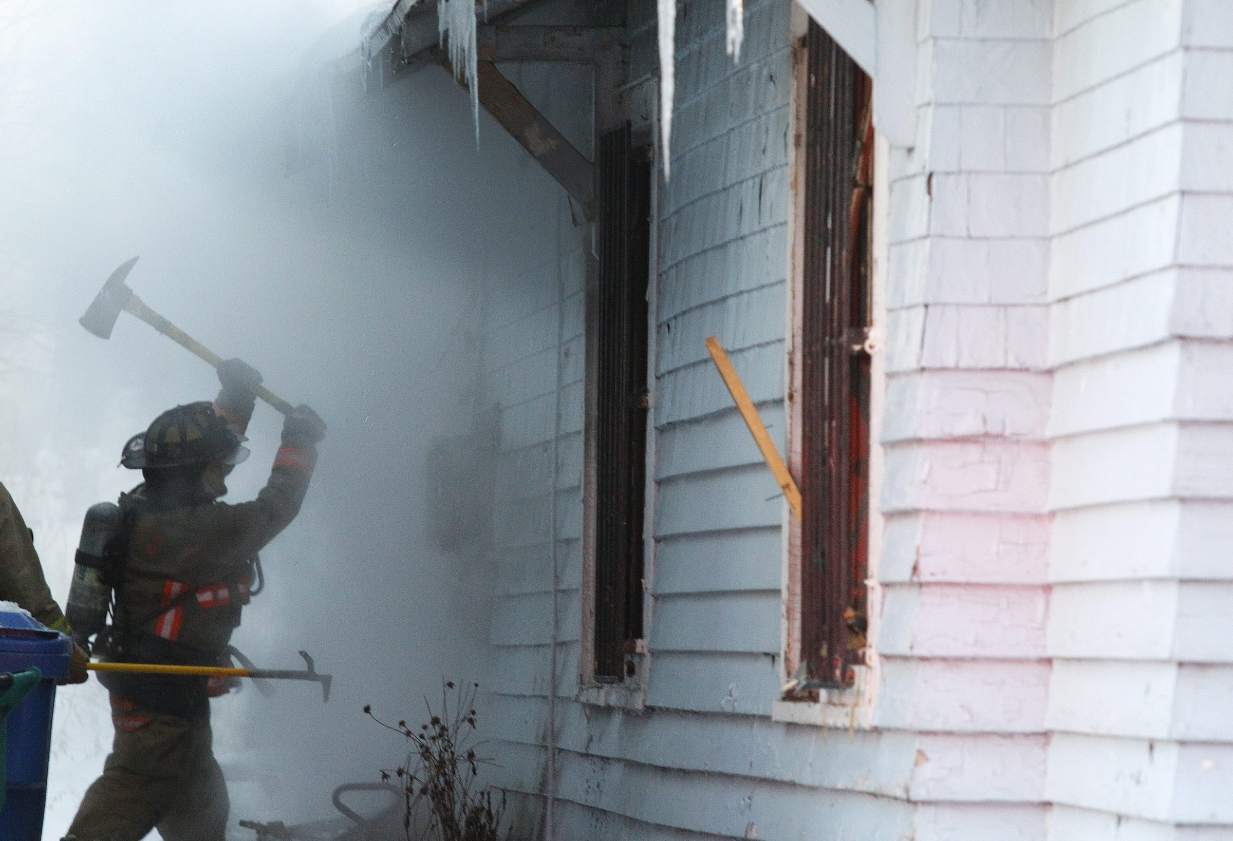 A Buffalo firefighter battles a fire on Leroy Avenue hampered by frozen fire hyrdants on Friday, Feb. 7, 2014, in Buffalo. (Harry Scull Jr./Buffalo News)