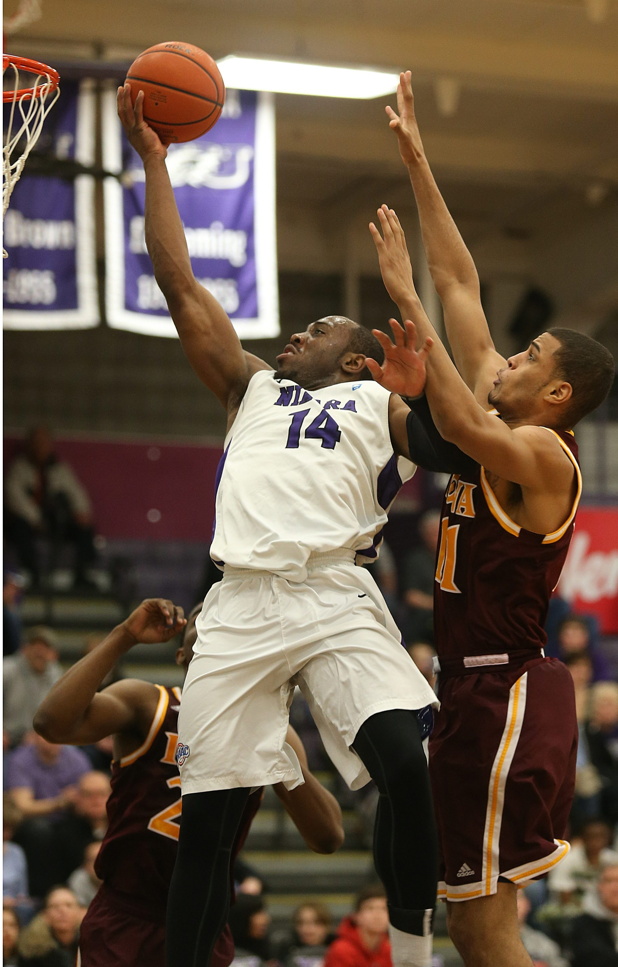 Niagara's Rayvon Harris goes to the hoop under pressure from Grant Ellis of Iona.  The Gaels won the game at the Gallagher Center, 90-89.