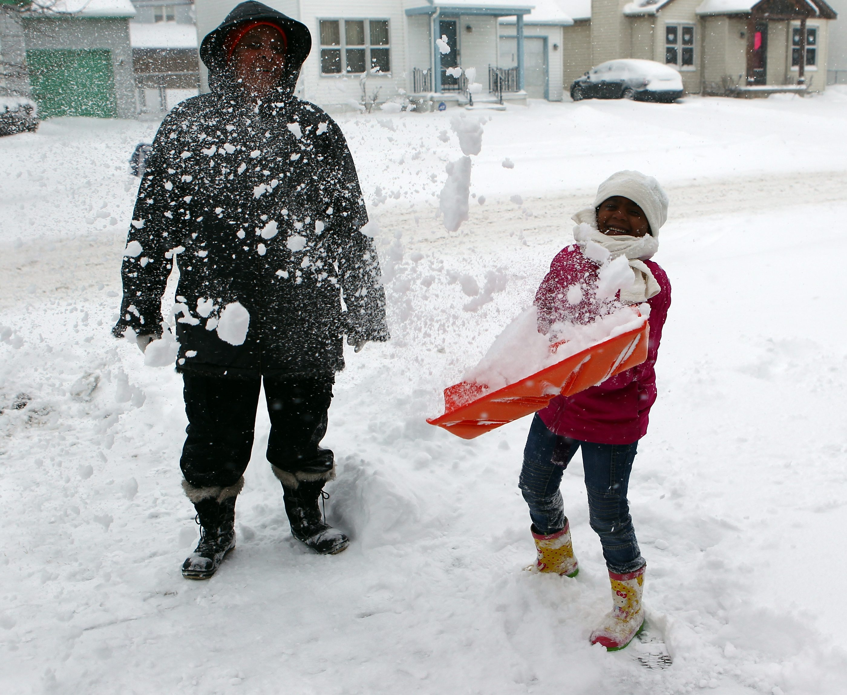 Symone Allen and her grandmother Joyce McKoy shovel their sidewalk in front of their home on South Division Street on Wednesday. (James P. McCoy/Buffalo News)
