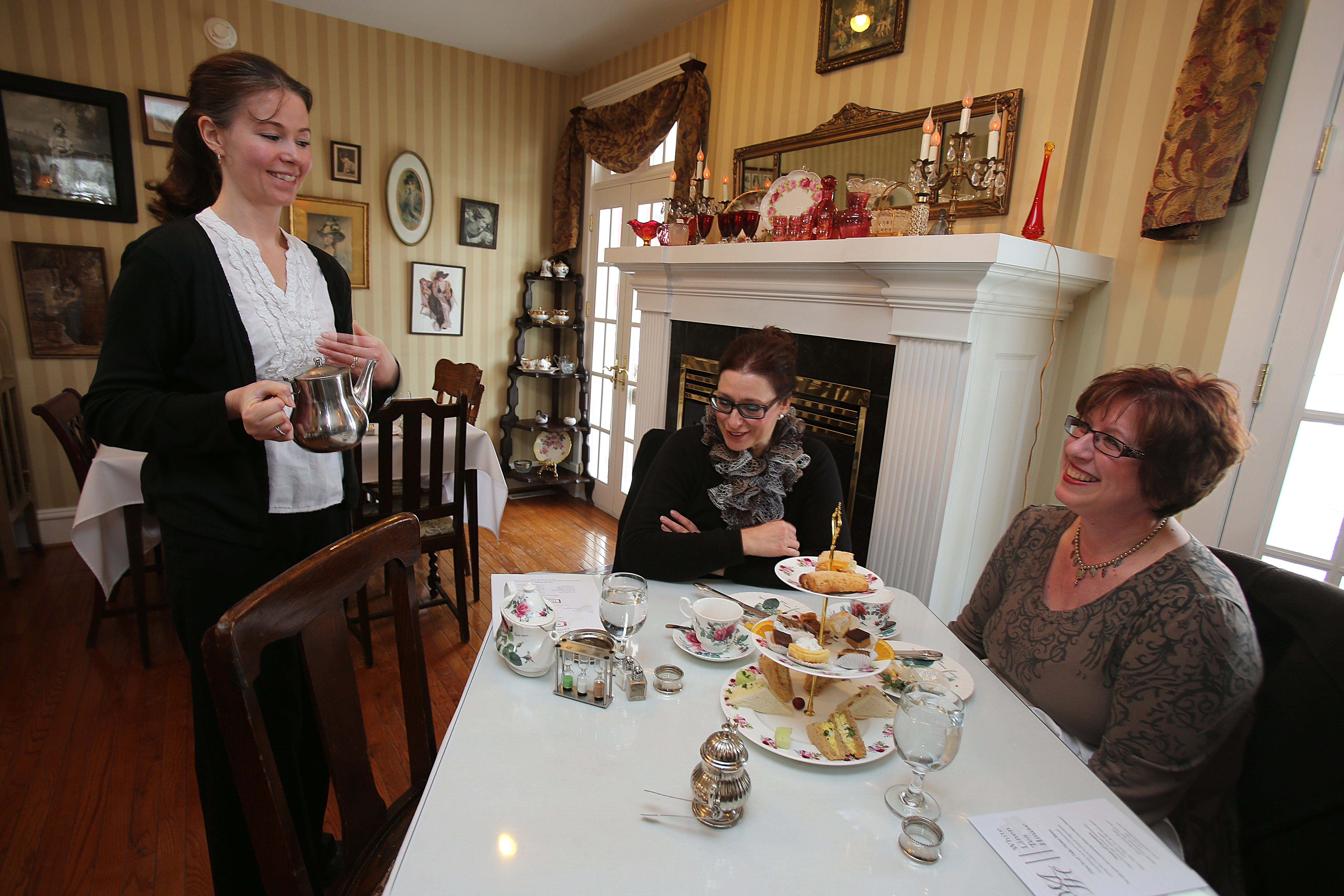 Server Tracy Bauch, left, tends to customers Dimitra Sergakis, middle, of Grand Island, and Kathy Stromecki, of Colden, in the White Linen Tea House at 6610 Shawnee Road in Wheatfield.