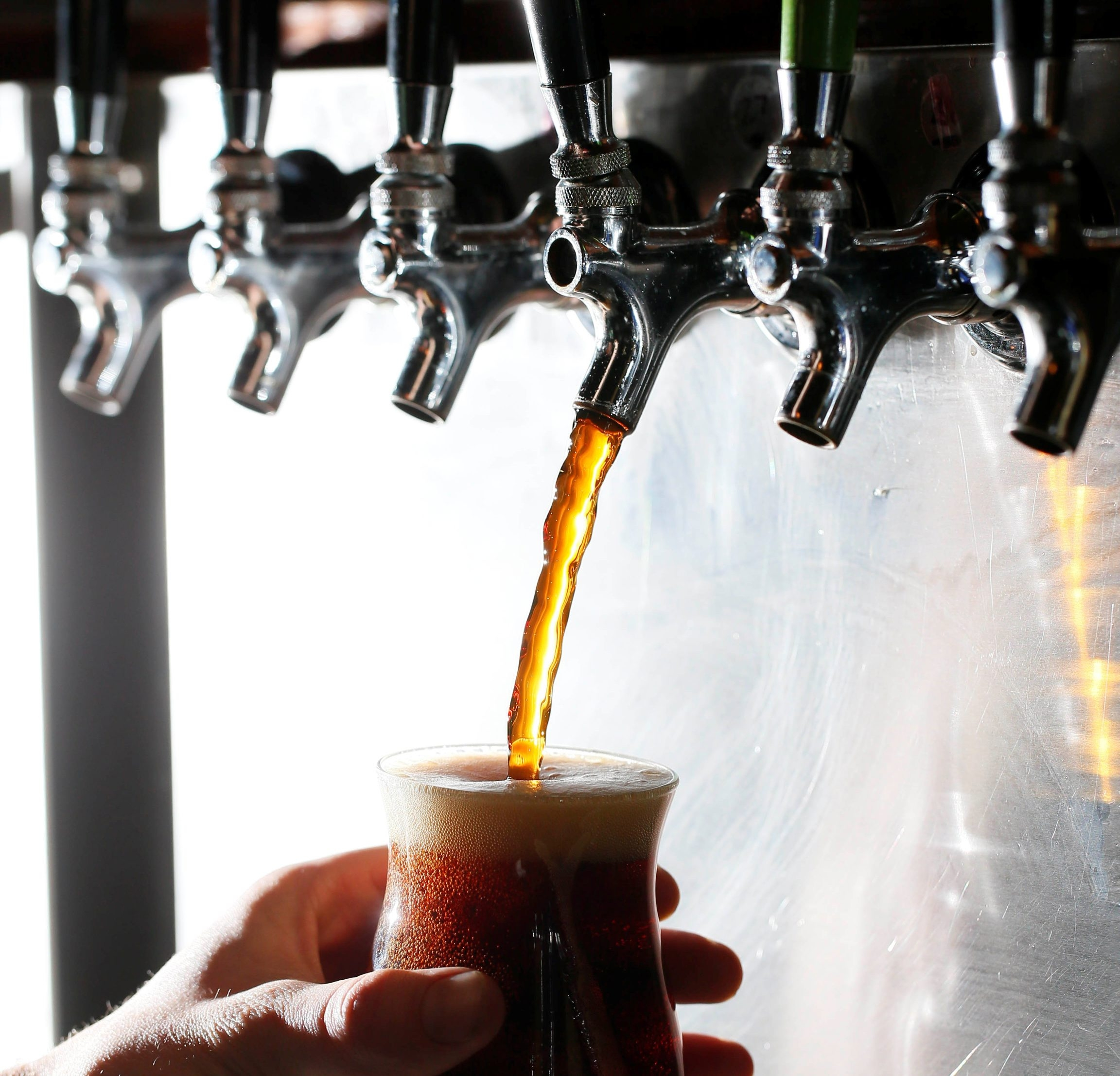 A bartender pours draft beers at the Blue Monk on Elmwood Avenue in this file photo.