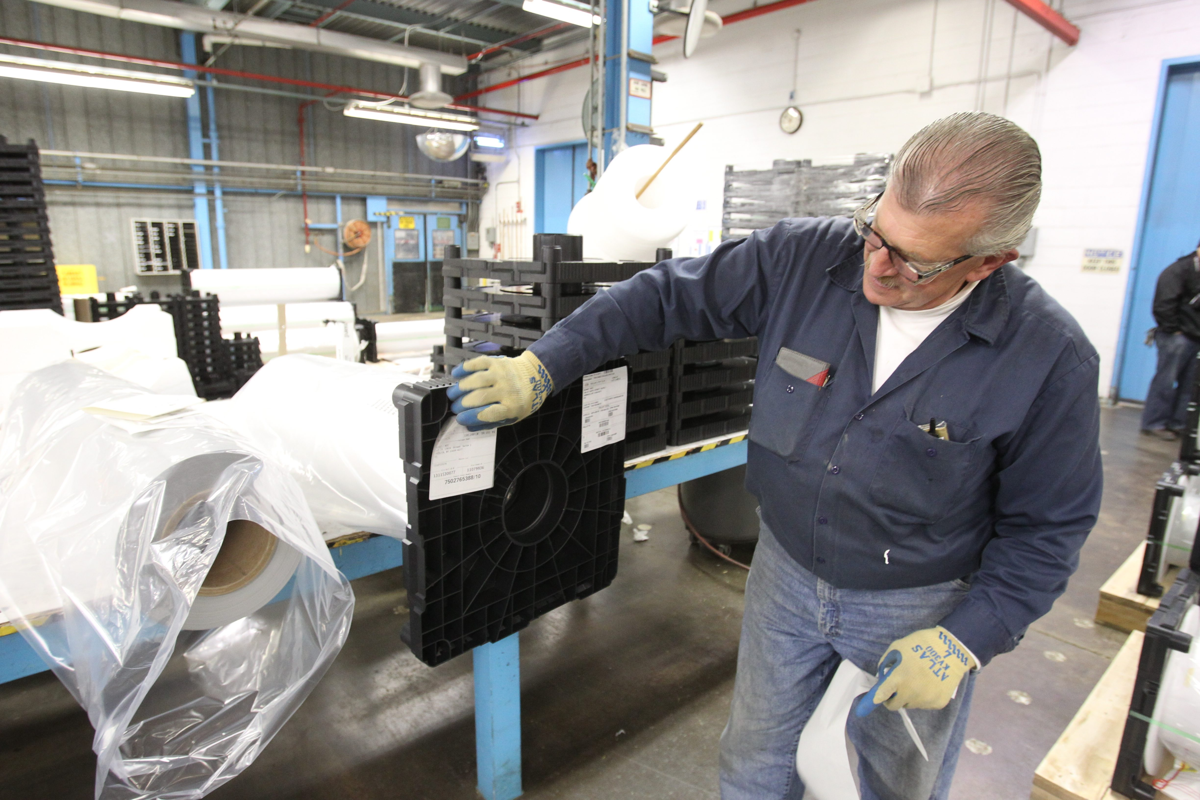 Tom Meaney, production operator at Yerkes finishing area, gets rolls of Tedlar ready for shipping. The site also has a Corian line.