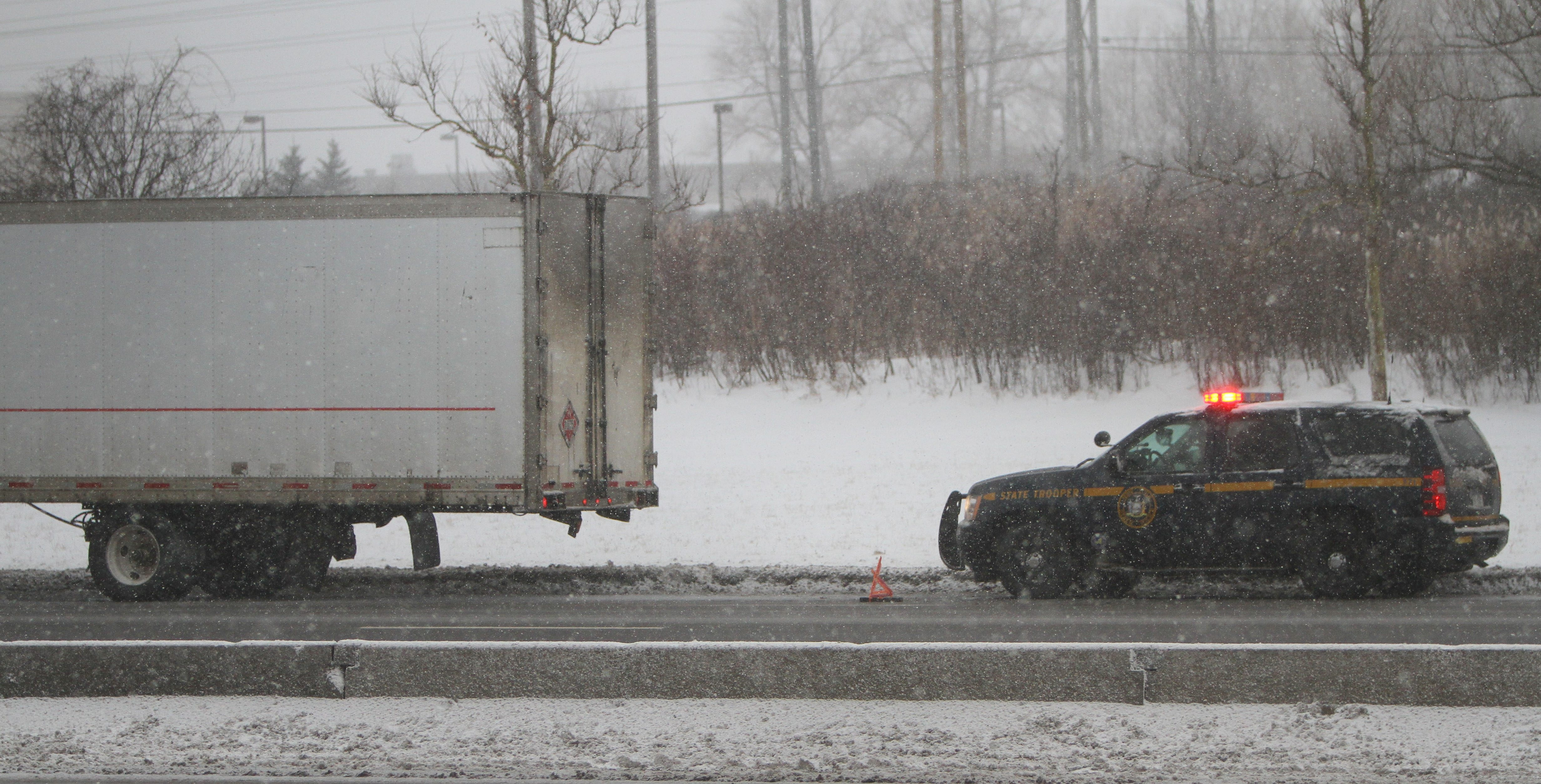State Troopers investigate the accident on the Thruway where a truck lost an axle near Walden Avenue in Cheektowaga this morning.