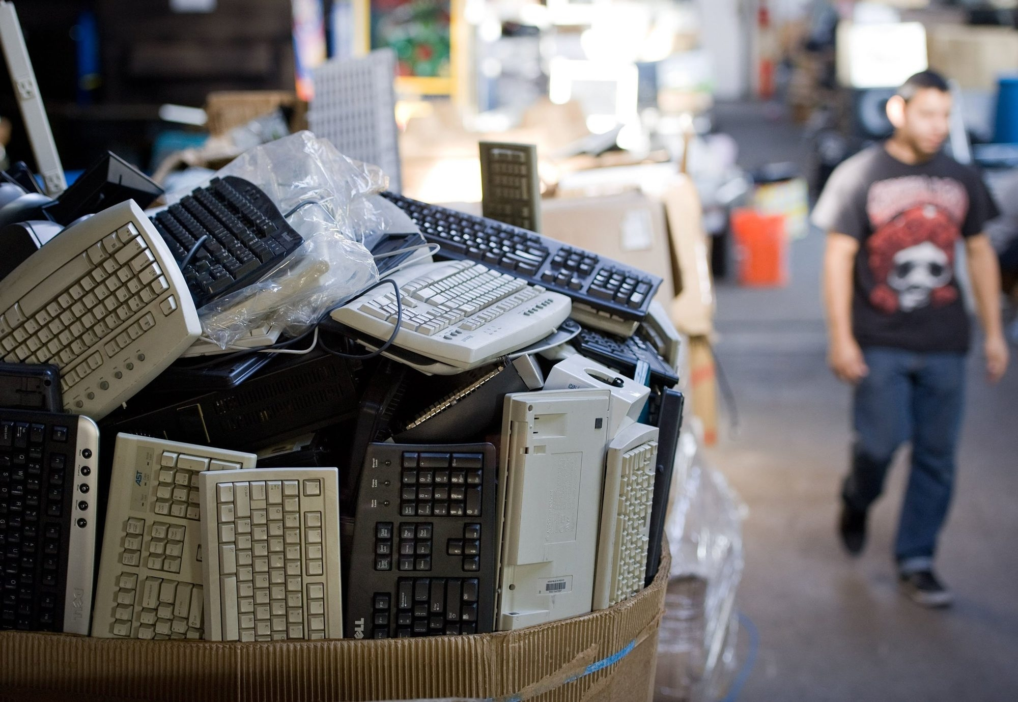 Old computer keyboards fill a box in a business warehouse in Santa Ana, Calif. In California, e-waste is recycled with funds paid by consumers as a fee when they purchase electronics.