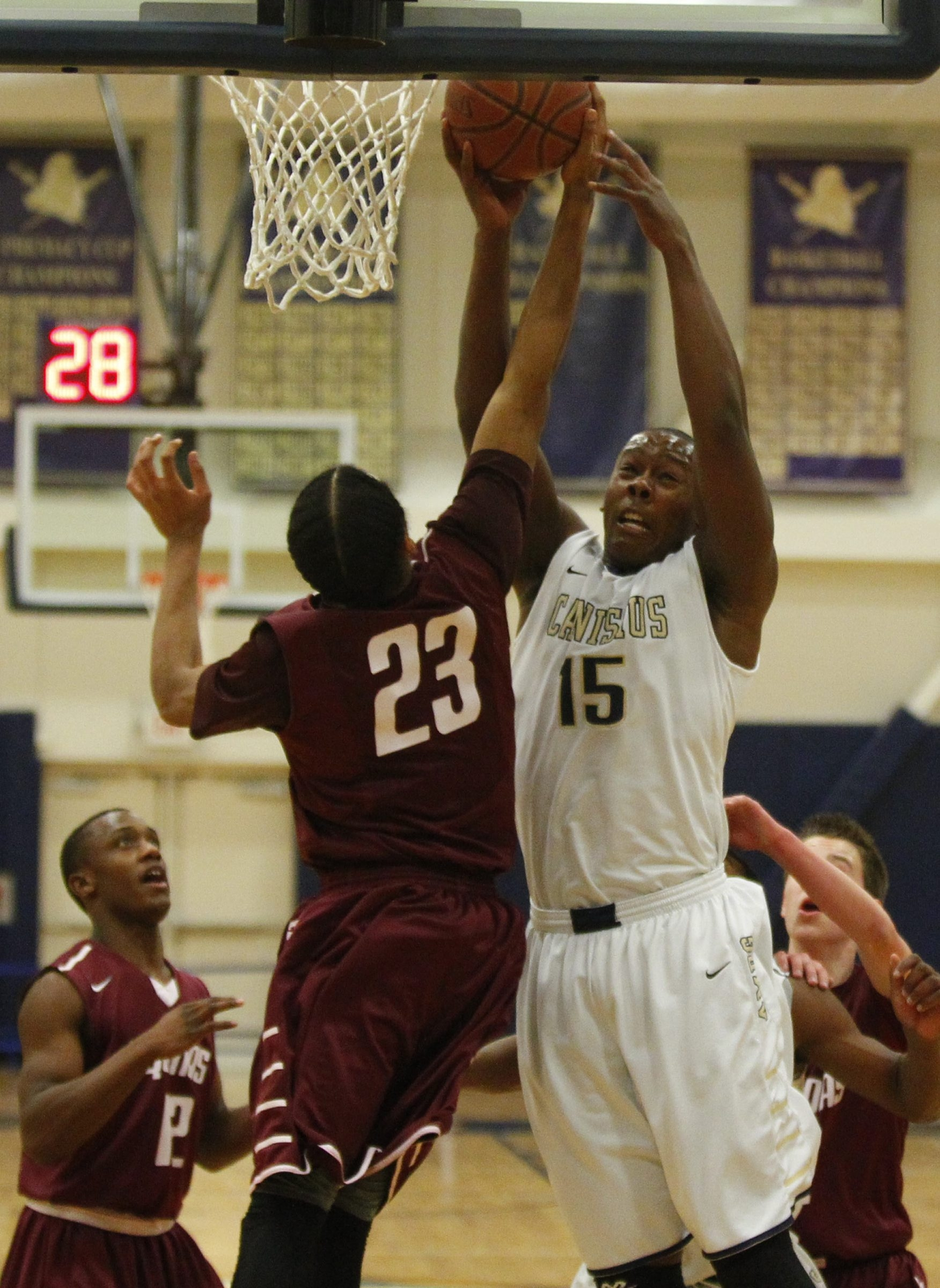TJ Wheatley (15) and D.J. Roberts of Aquinas battle for a rebound during the Crusaders' victory.