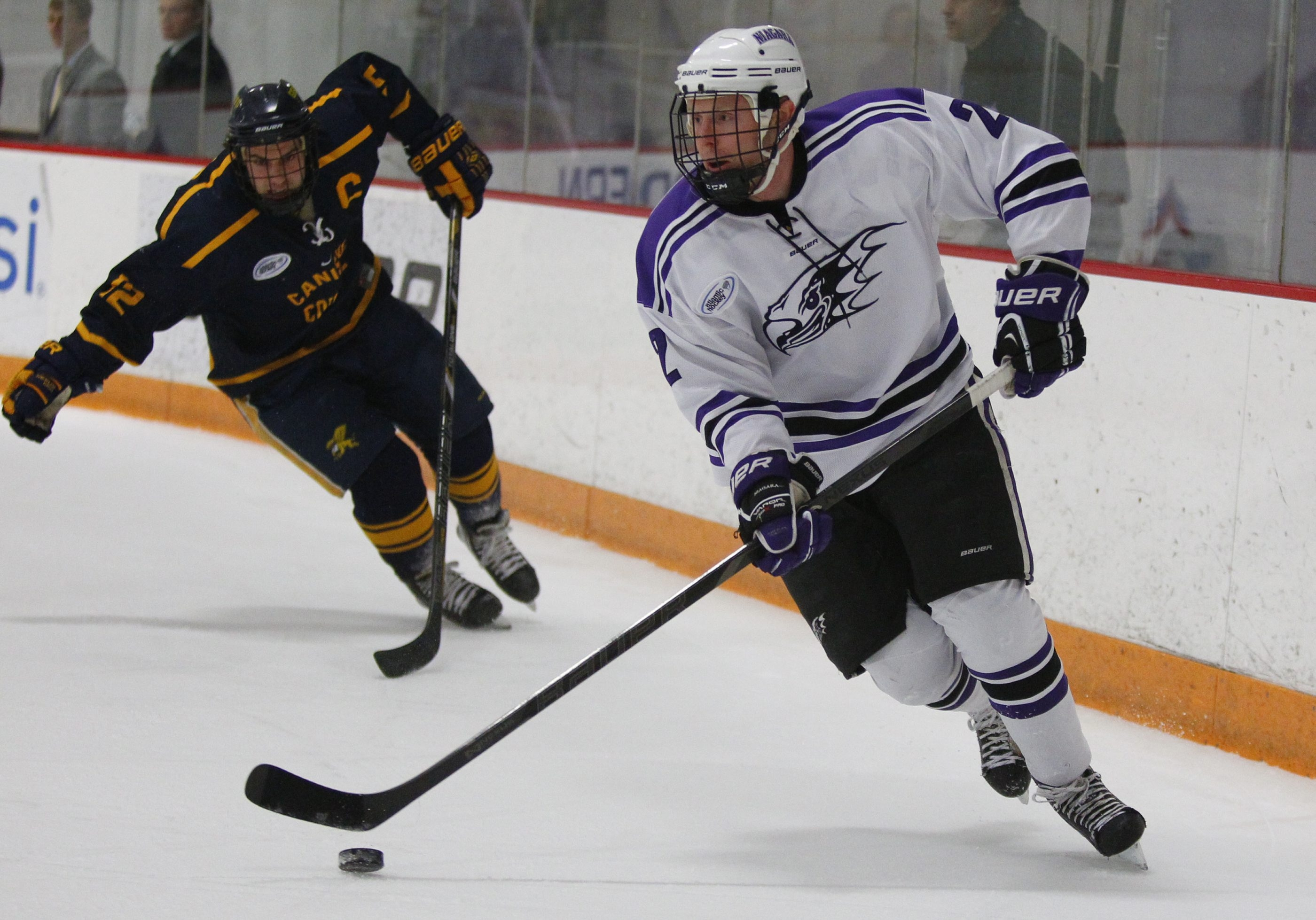 Niagara's Kevin Ryan moves the puck past Canisius player Ryan Bohrer (12) Thursday during their game at Dwyer Arena.