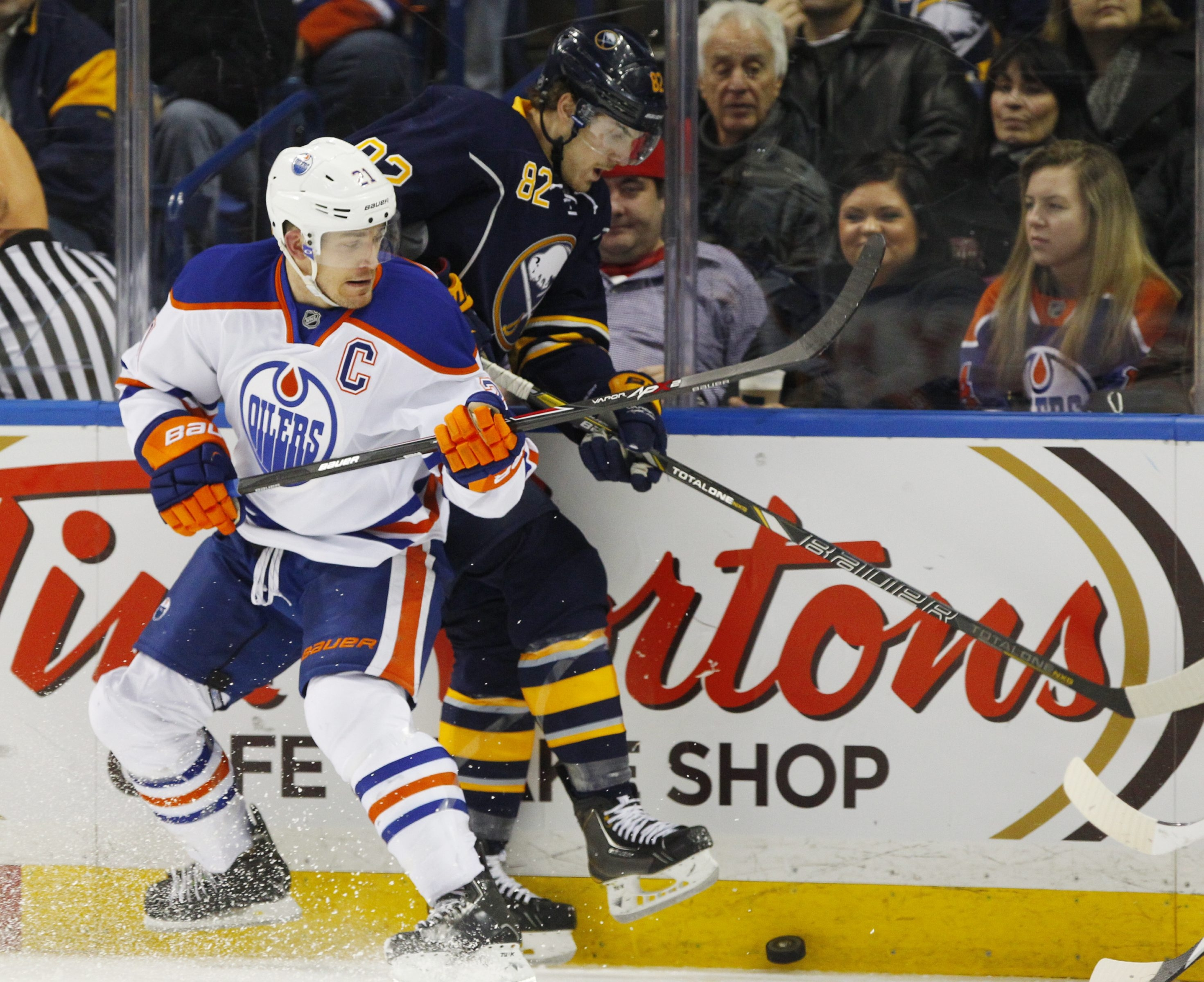 Buffalo's Marcus Foligno (82) and Edmonton's Andrew Ference (21) battle for a puck.