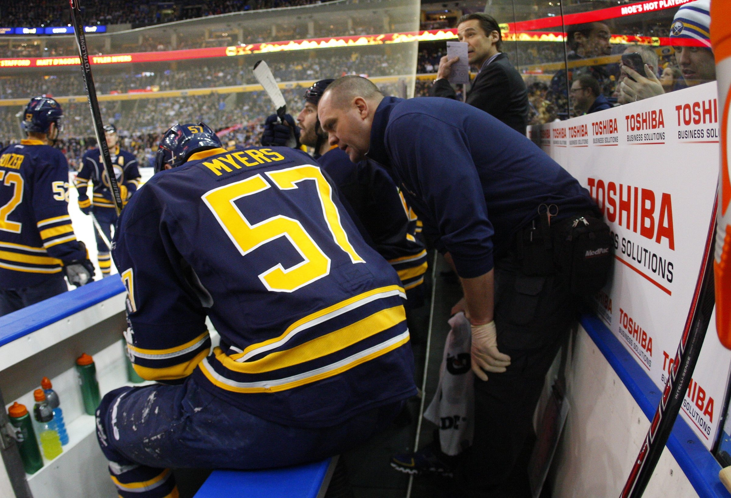 Trainer Tim Macre checks on Tyler Myers after he hit the boards hard on Monday night.