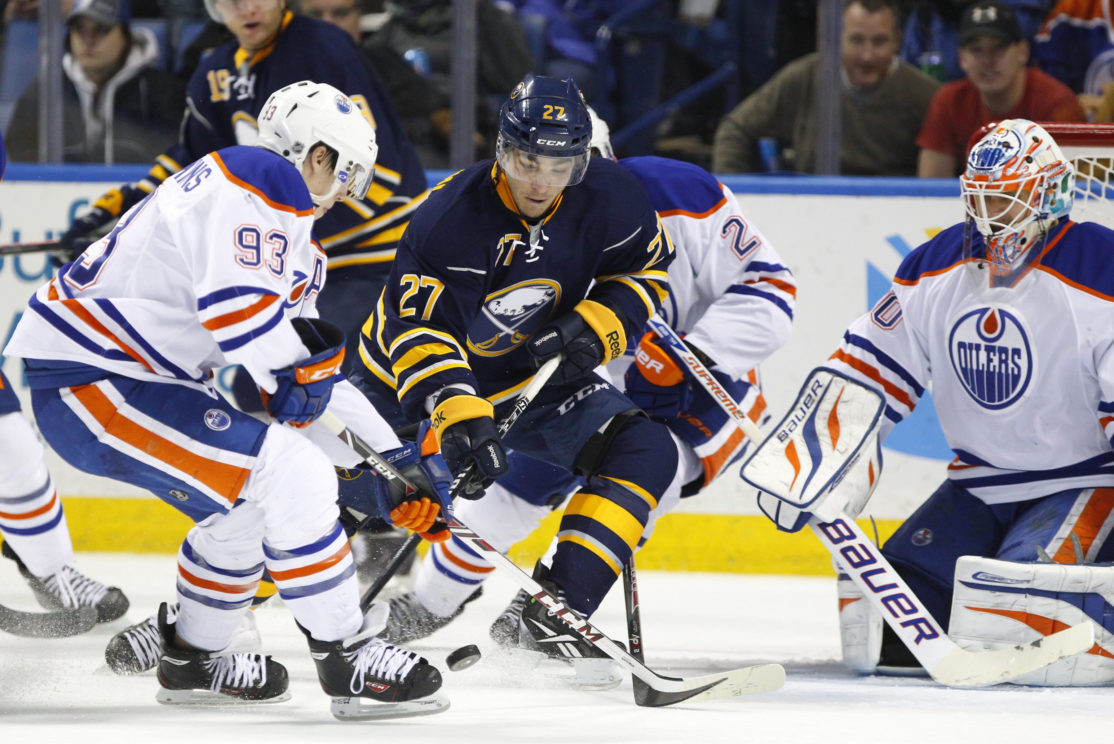 Sabres' forward Matt D'Agostini (27) moves the puck past the Oilers' Ryan Nugent-Hopkins (93) during Monday's game.