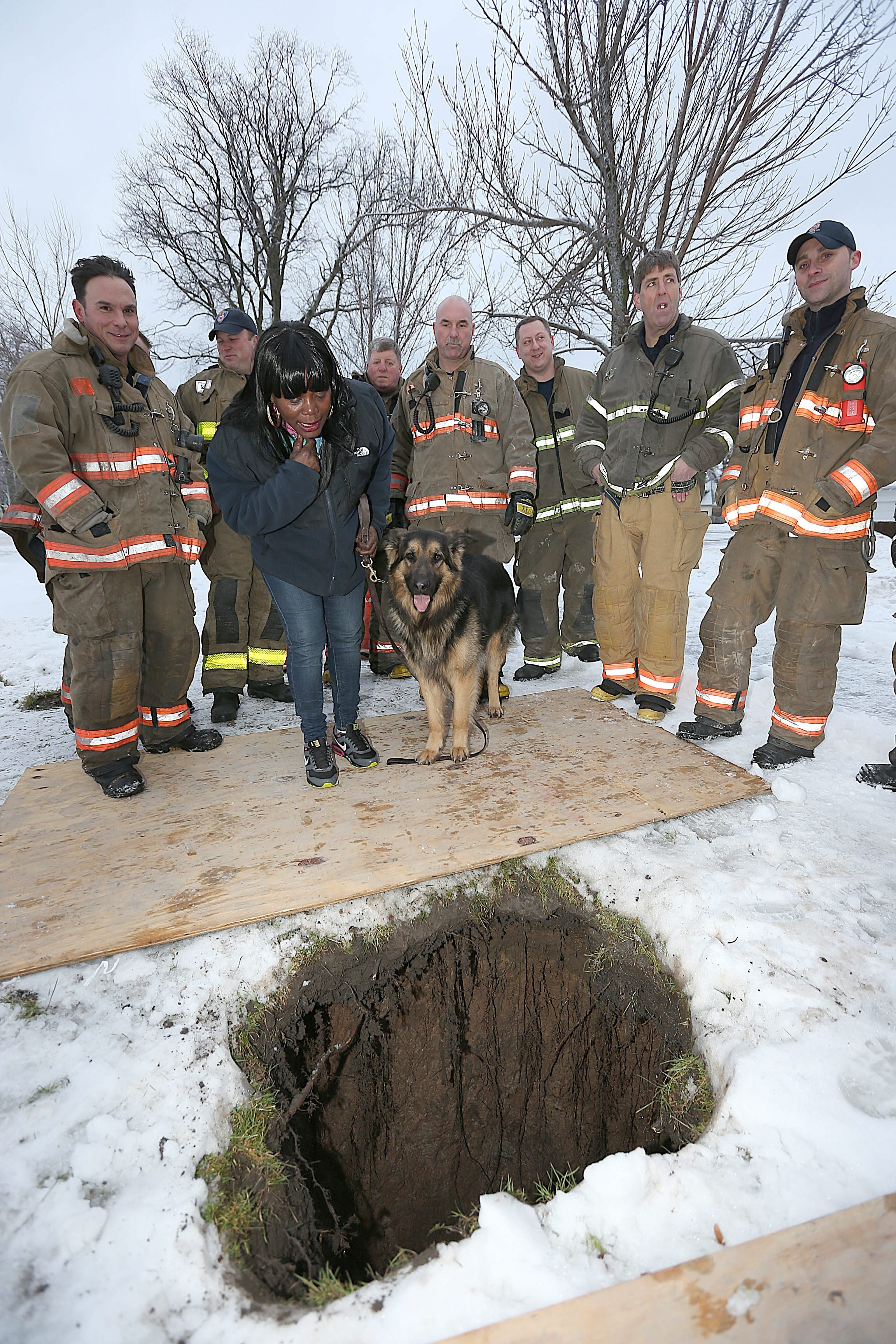 Buffalo firefighter Michael Paveljack, far left, and fellow members of the Technical Rescue Team saved German shepherd Mack from this sinkhole in Martin Luther King Park on Sunday. With Mack is his owner, Mattie Moore.
