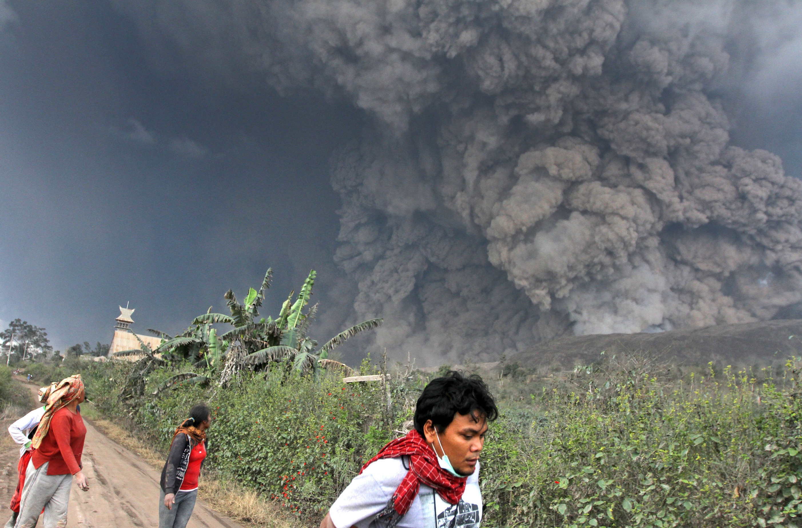 Villagers and a journalist prepare to flee as Mount Sinabung releases pyroclastic flows during an eruption in Namantaran, North Sumatra, Indonesia, on Saturday. The volcano, dormant for 400 years, erupted in August 2010.