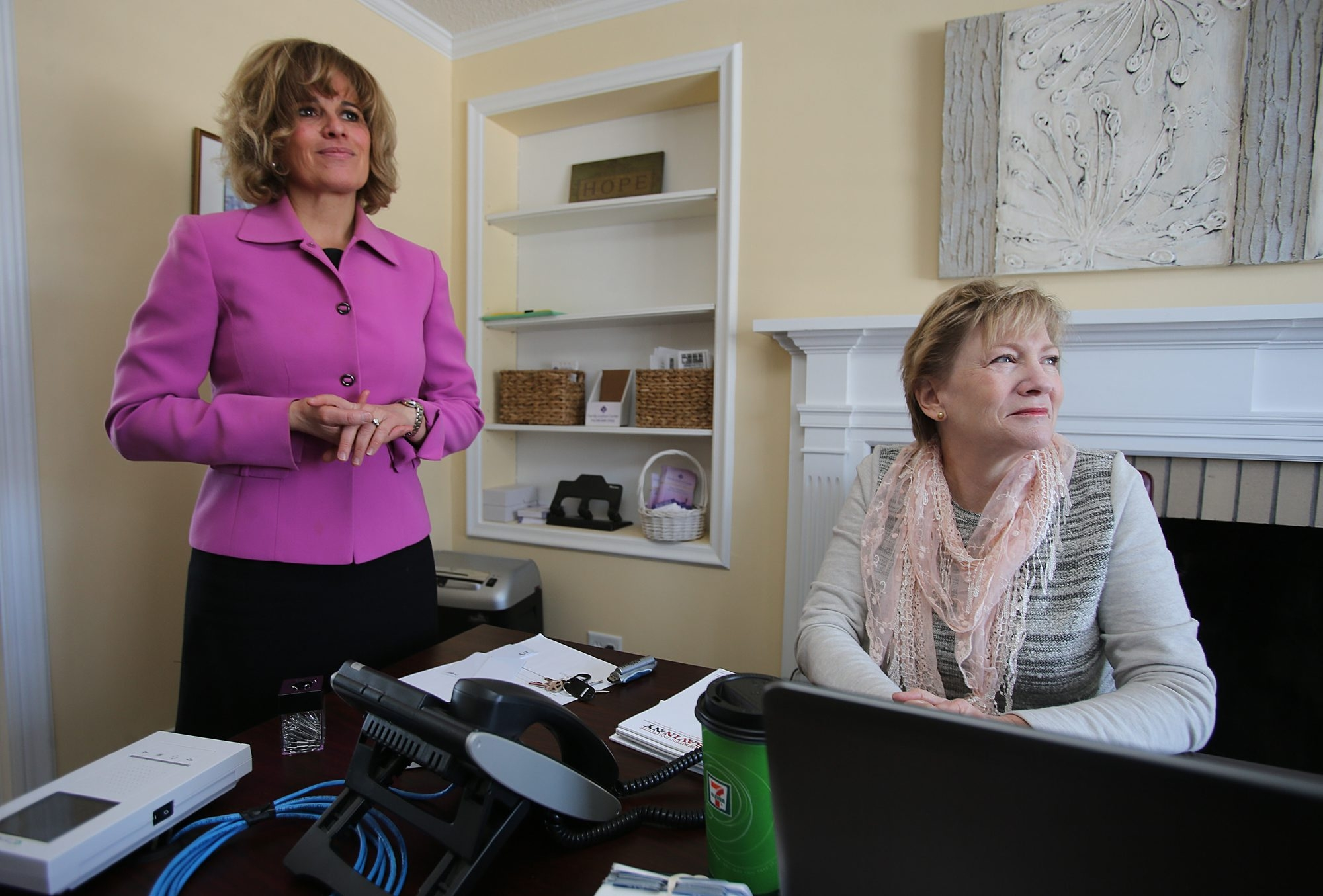 Mary Travers Murphy, executive director of the Family Justice Center, left, talks with volunteer Grace Smith in the new Amherst satellite office on Thursday.