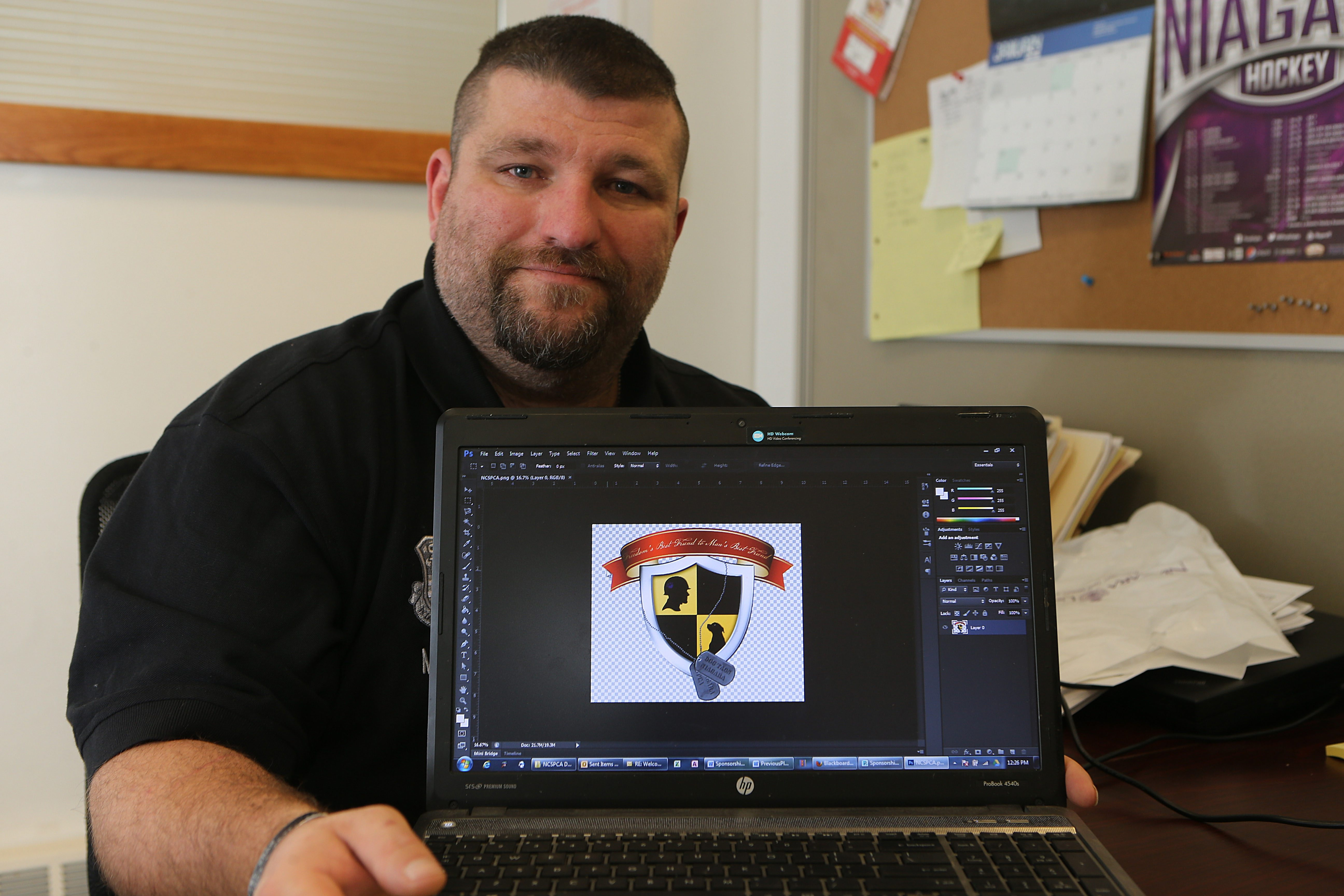 Karl Hinterberger in the Veterans Services Office in St. Vincent's Hall on the Niagara University campus in Lewiston with the design he created for Dog Tags Niagara, a veterans rehabilitation program.