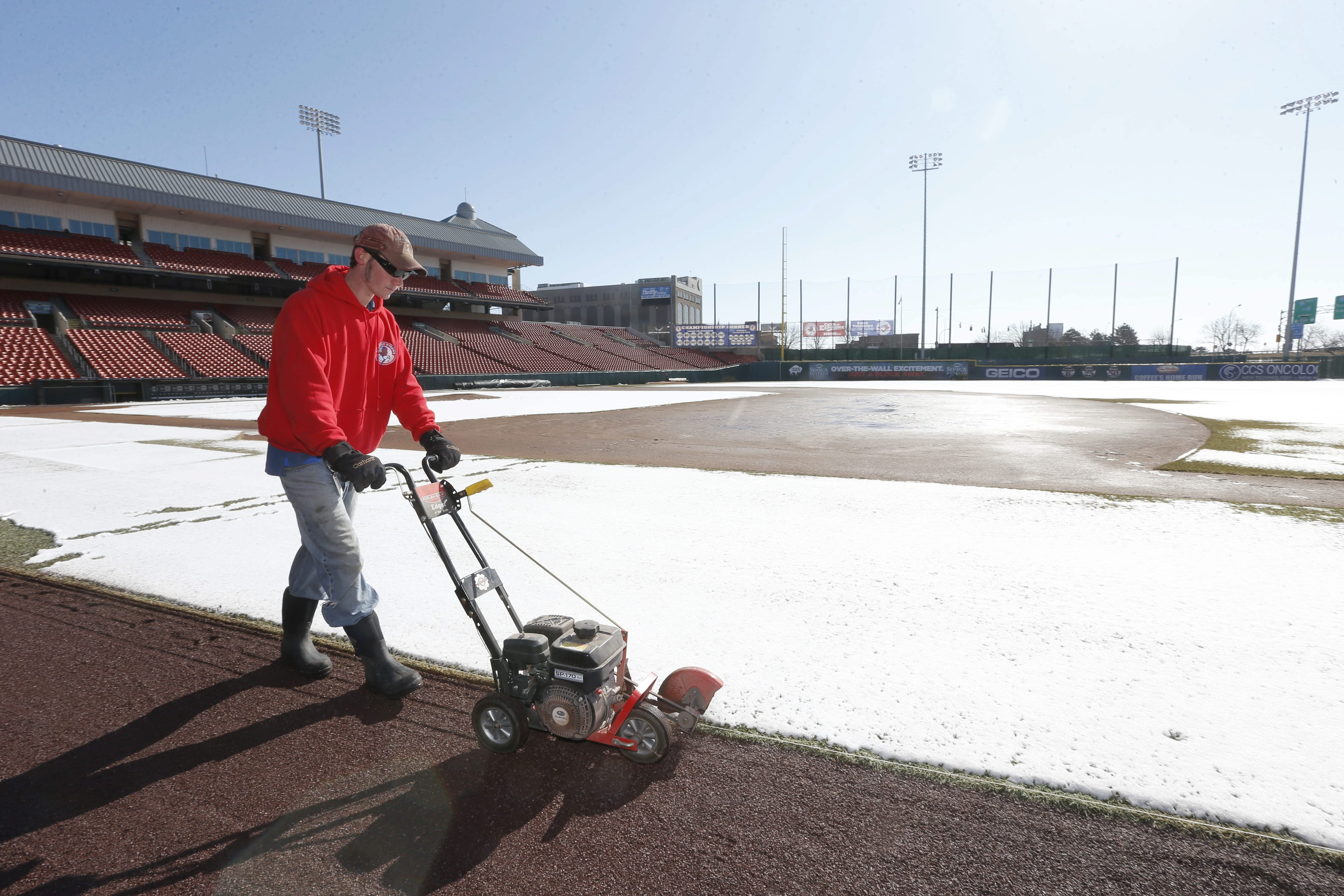 Assistant groundskeeper Jeremy Atkins edges the warning track at Coca-Cola Field  on Monday. The recent snow didn't help, but with warmer temperatures coming, the field is expected to be ready to go. See a photo gallery at BuffaloNews.com.