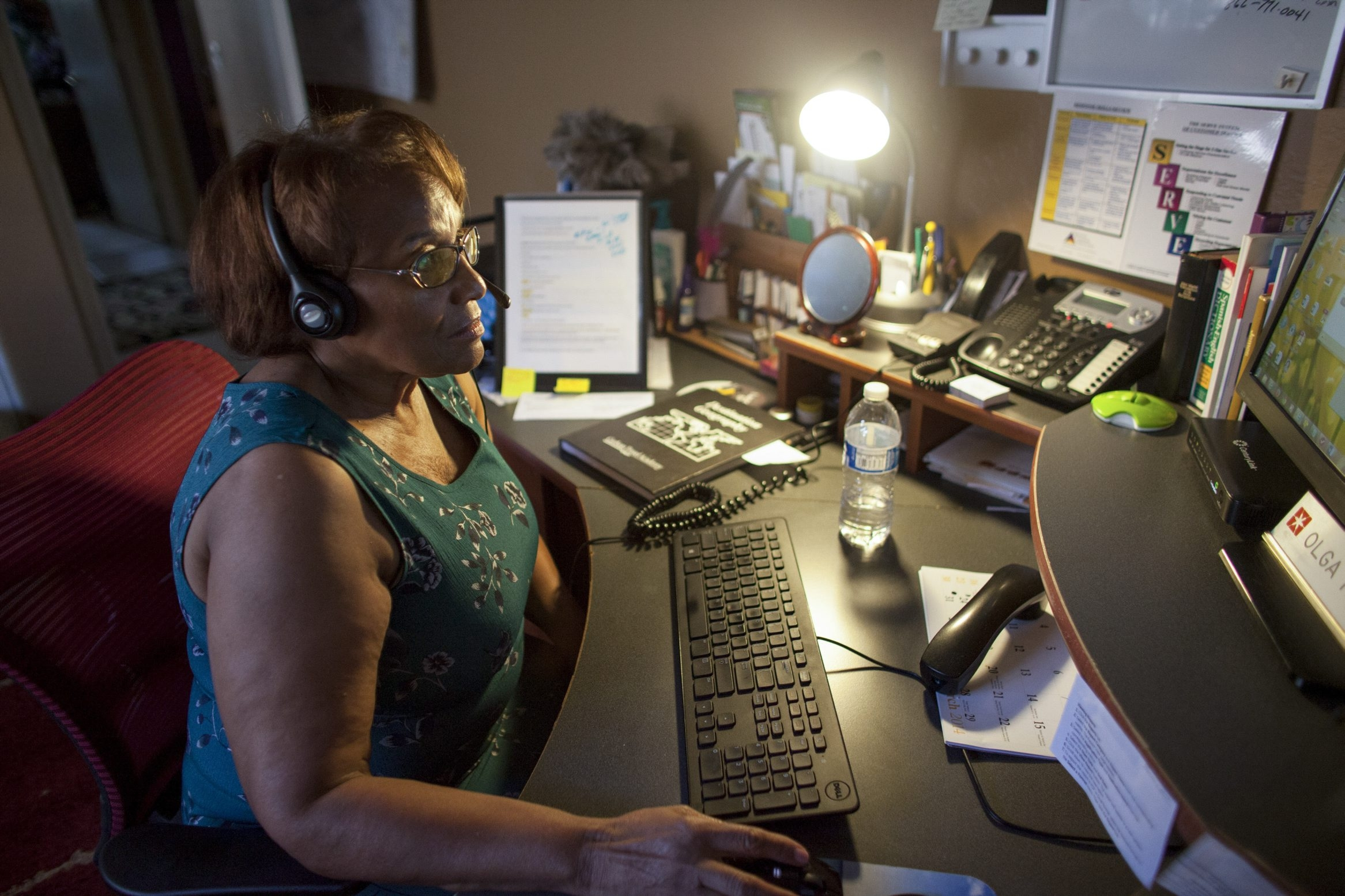 Olga Howard, 71, who works 25 to 30 hours a week from home as a customer service representative, helps a client over the phone in Tolleson, Ariz. The Bureau of Labor Statistics says 24 percent of workers in the U.S. do some or all their work from home.